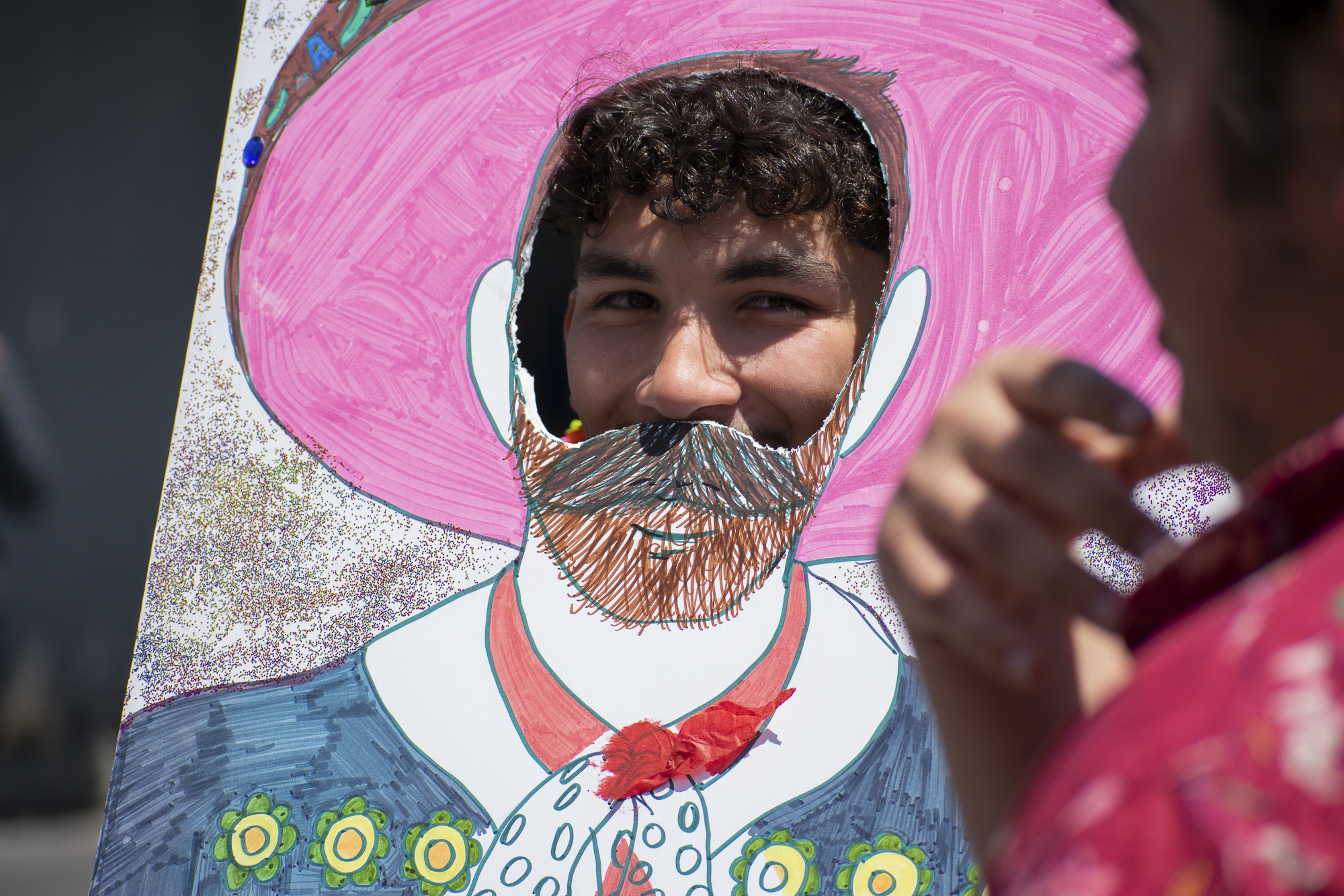 Christian Escovar poses for a friend in front of the Adelante Club's booth on the quad at Santa Monica College during Club Row on Thursday, April 26, 2018 in Santa Monica, California. With over 60 clubs in attendance, the day is meant to encourage clubs to showcase what they've been doing over the semester for students. (Ethan Lauren/Corsair Photo)