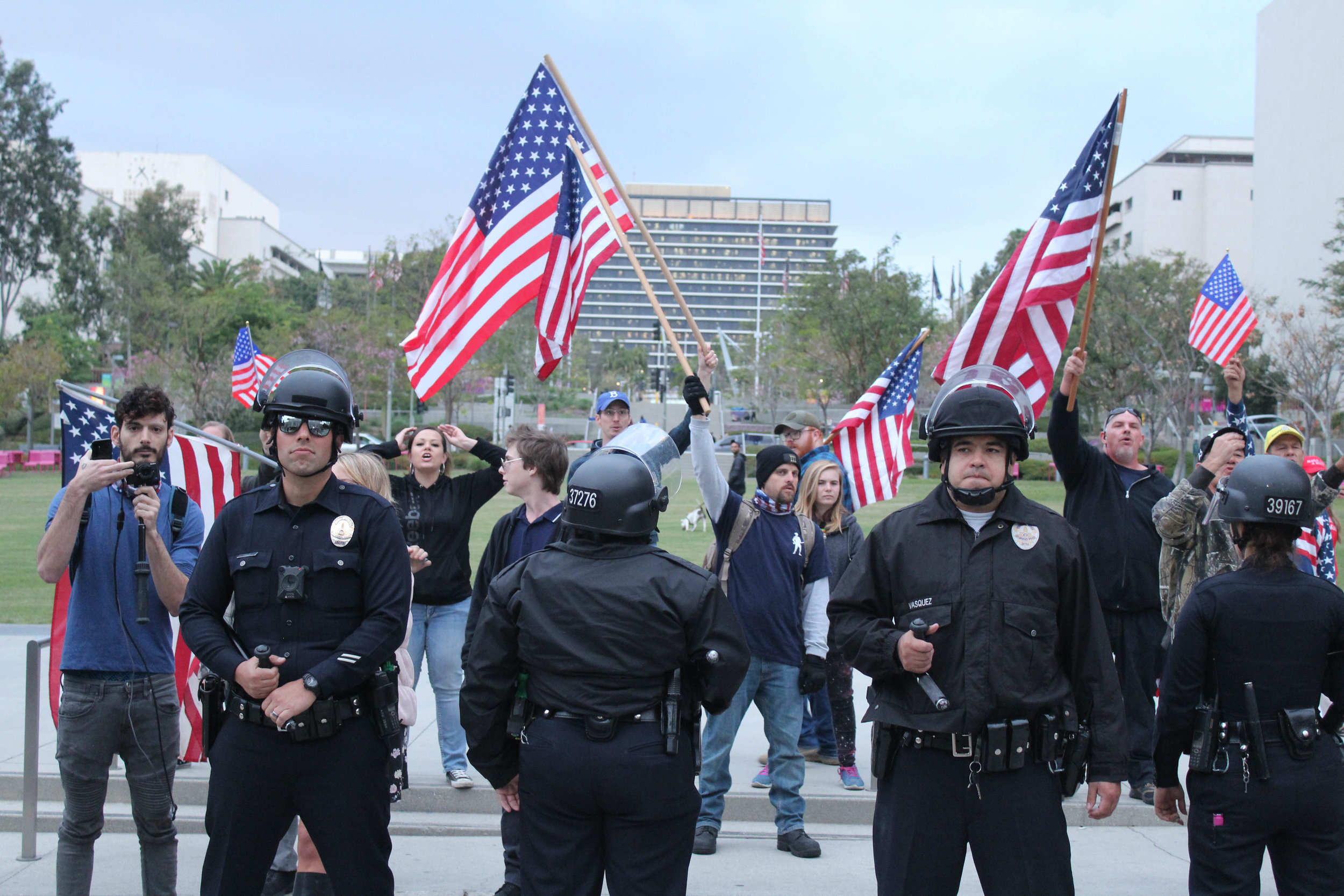 LAPD officers create a barrier around the few Donald Trump supporters in downtown Los Angeles on May 1, 2018. (Daniel Farr/Corsair Photo).
