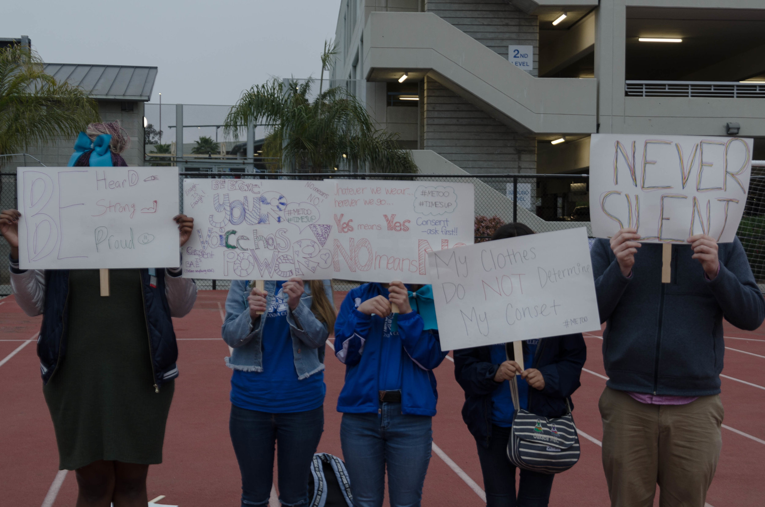 SMC students and faculty hold up signs made for March 23rd's Take Back the Night event at the SMC football field. Participants in the event, which highlights sexual assault on college campuses, concealed their faces in order to preserve their anonomity.(Reed Curtis/Corsair Photo)
