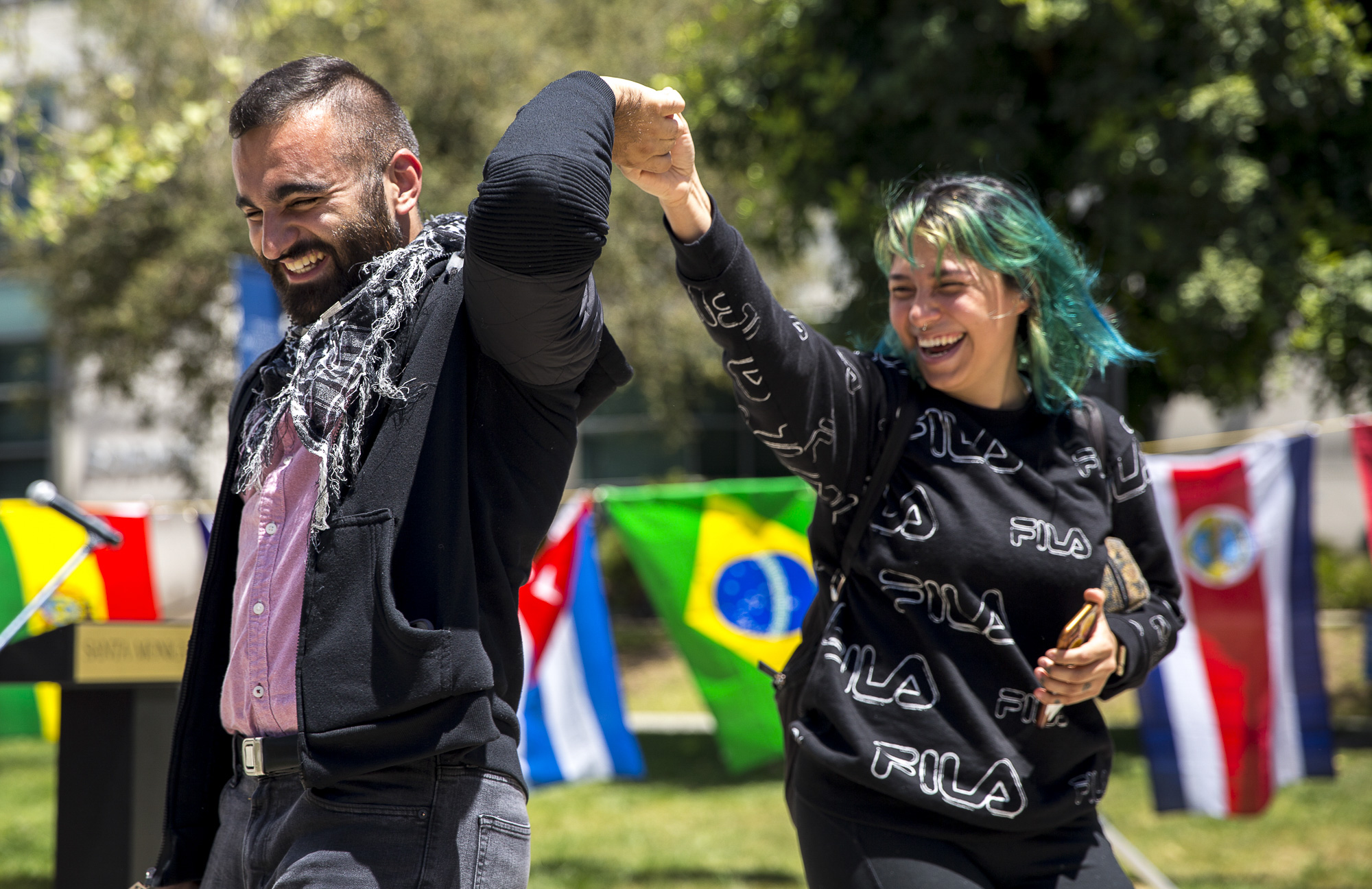 """Associated Student Director of Student Advocacy Alexa Benavente (right) dances with newly elected Associated Student Vice President Hesham Jarmakani (left) during the Cinco de Mayo Celebratory event organized by Santa Monica College club (SMC) """"Adelante"""" in front of the clock tower on the SMC main campus on Thursday, May 3 2018.  This event was put together by the Santa Monica College club """"Adelante,"""" whose goal at the event was to inform students about the origins of Cinco De Mayo and put to rest the stereotypes that come with the holiday, specifically the misperception that it is a day of independence for Mexico and also that is just a drinking holiday in the United States. (Matthew Martin/Corsair Photo)"""