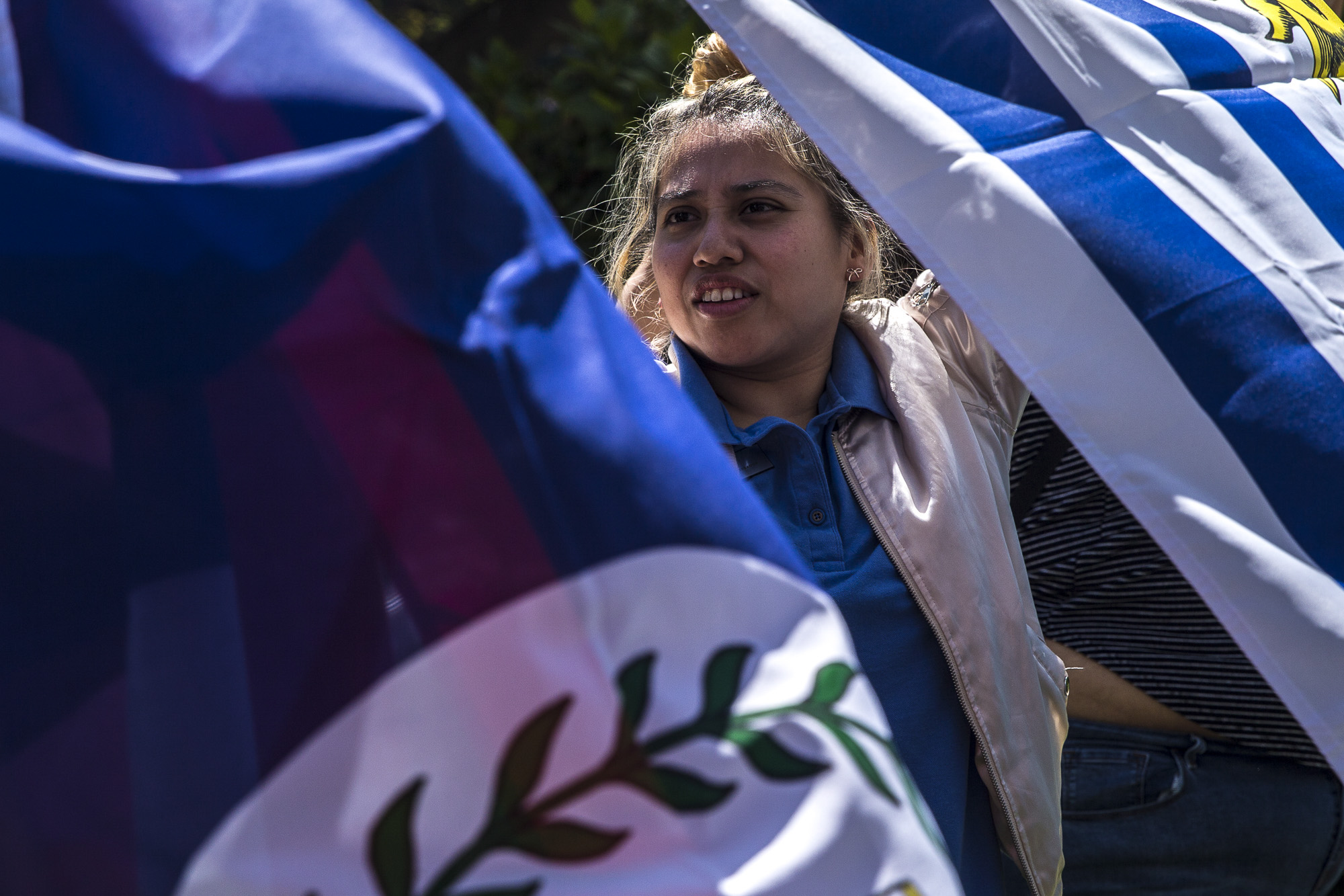 """Santa Monica College students and """"Adelante"""" club members help set up flags and decorations for the Cinco de Mayo Celebratory event that took place in front of the clock tower on the SMC main campus on Thursday, May 3 2018.  This event was put together by the Santa Monica College club """"Adelante,"""" whose goal at the event was to inform students about the origins of Cinco De Mayo and put to rest the stereotypes that come with the holiday, specifically the misperception that it is a day of independence for Mexico and also that is just a drinking holiday in the United States. (Matthew Martin/Corsair Photo)"""