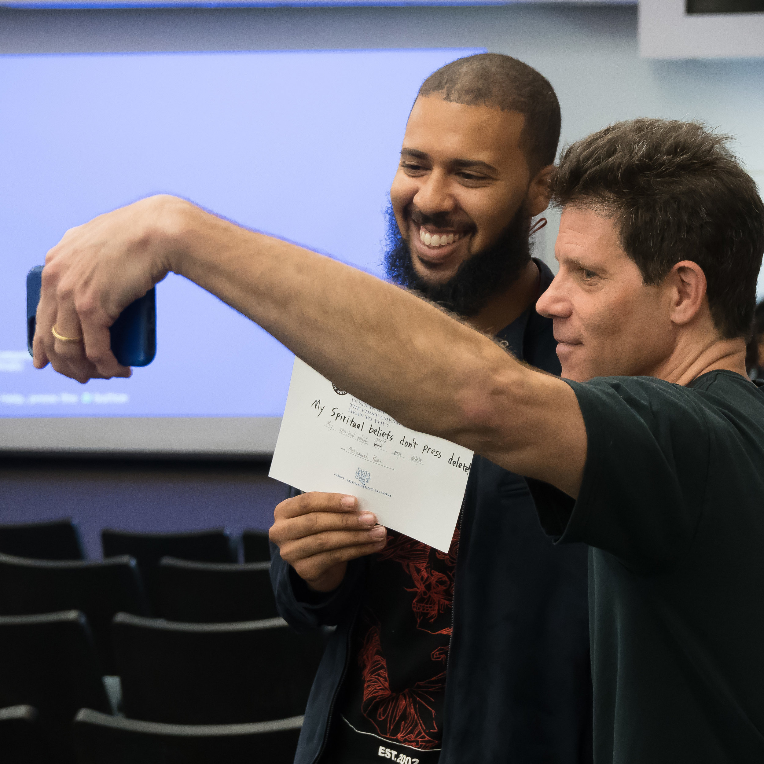 """Larry Smith (right) founder of Six-Word Memoirs, takes a selfie with student Mohammed Khan at Santa Monica College in Santa Monica, California on May 3, 2018. Smith spoke about summarizing the meaning of the First Amendment in six words, and was especially taken with Khan's, which was, """"My spiritual beliefs; don't press delete,"""" referring to how Khan is often mistaken for Mulsim, when he is, in fact, Christian.  (Helena Sung/Corsair Photo)."""
