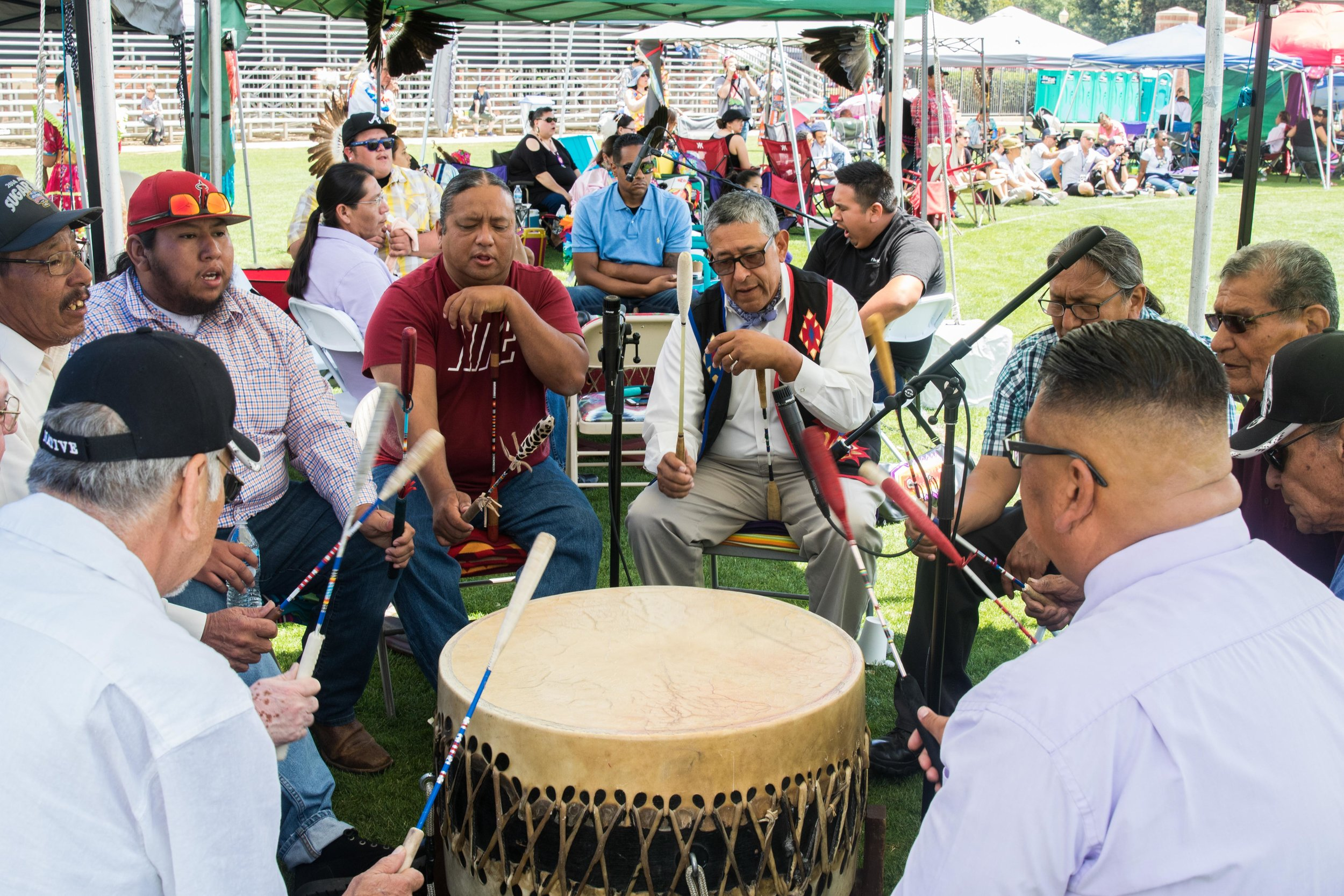 Members of various Indigenous tribes join together to play the drums for one of the numerous dance routines at the thirty-third annual UCLA Pow-Wow. Drums and dancing are used to give thanks and pay respect to The Creator in many Indigenous Cultures. (Zane Meyer-Thornton/Corsair Photo)