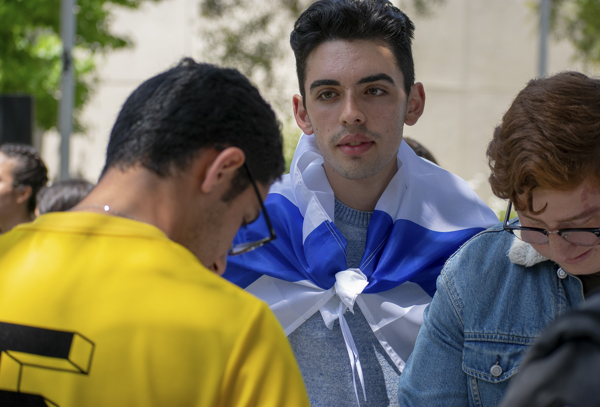 "Itzchak ""Isaac"" Maghen plays backgammon while wearing the flag of Israel on his back during an event put on by the Students Supporting Israel club at Santa Monica College on Thursday, May 10 in Santa Monica, California. The event was a celebration for the 70th anniversary of Israel's independence. (Ethan Lauren/Corsair Photo)"