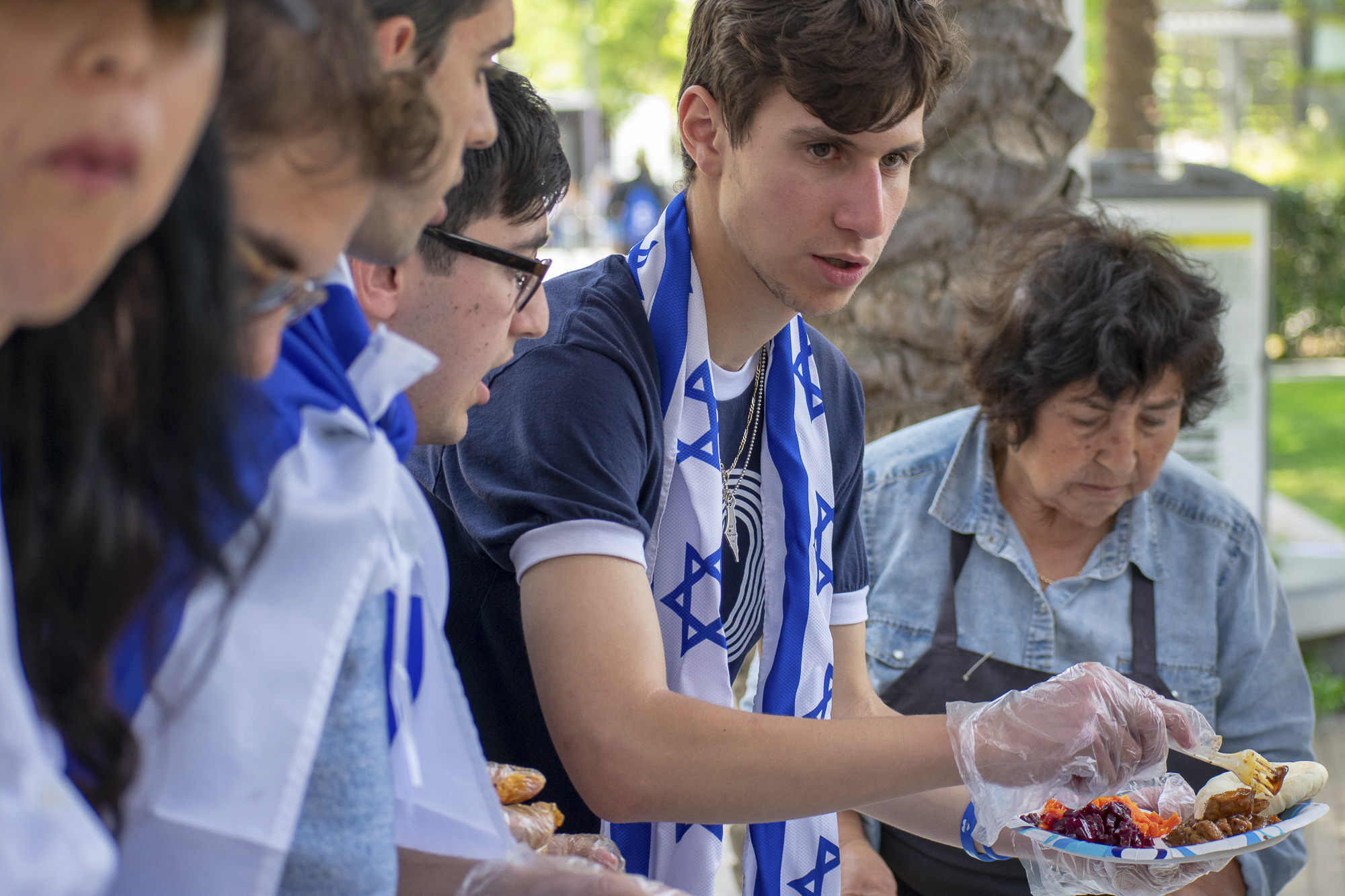 Food is served from the Ta-eem Grill in Los Angeles such as hummus and shawarma, which were provided to students for free during an event put on by the Students Supporting Israel club, including the president Justin Feldman, right, at the college on Thursday, May 10 in Santa Monica, California. The event was a celebration for the 70th anniversary of Israel's independence. (Ethan Lauren/Corsair Photo)