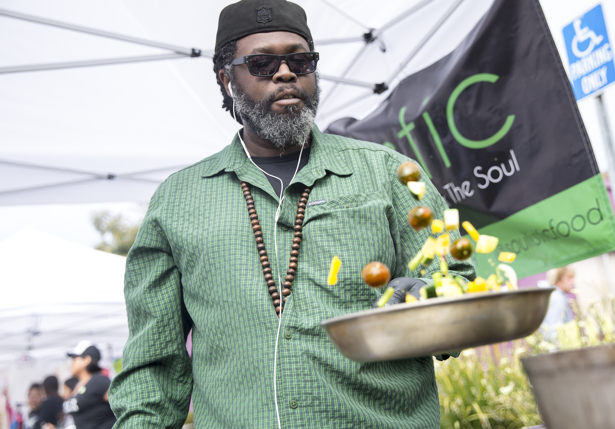 """Chef D. Dahm tosses a mix of vegan ingredients in a pan at the """"Soulistic Vegan Food"""" tent during the Pico Block Party festivities that took place at the 18th street Arts Center in Santa Monica, California on Saturday May 19, 2018. The Pico Block Party is a celebration of artists and cultures of the Pico neighborhood in Santa Monica with the festivities primarily focusing on youth artists and empowering youth voices. (Matthew Martin/Corsair Photo)"""