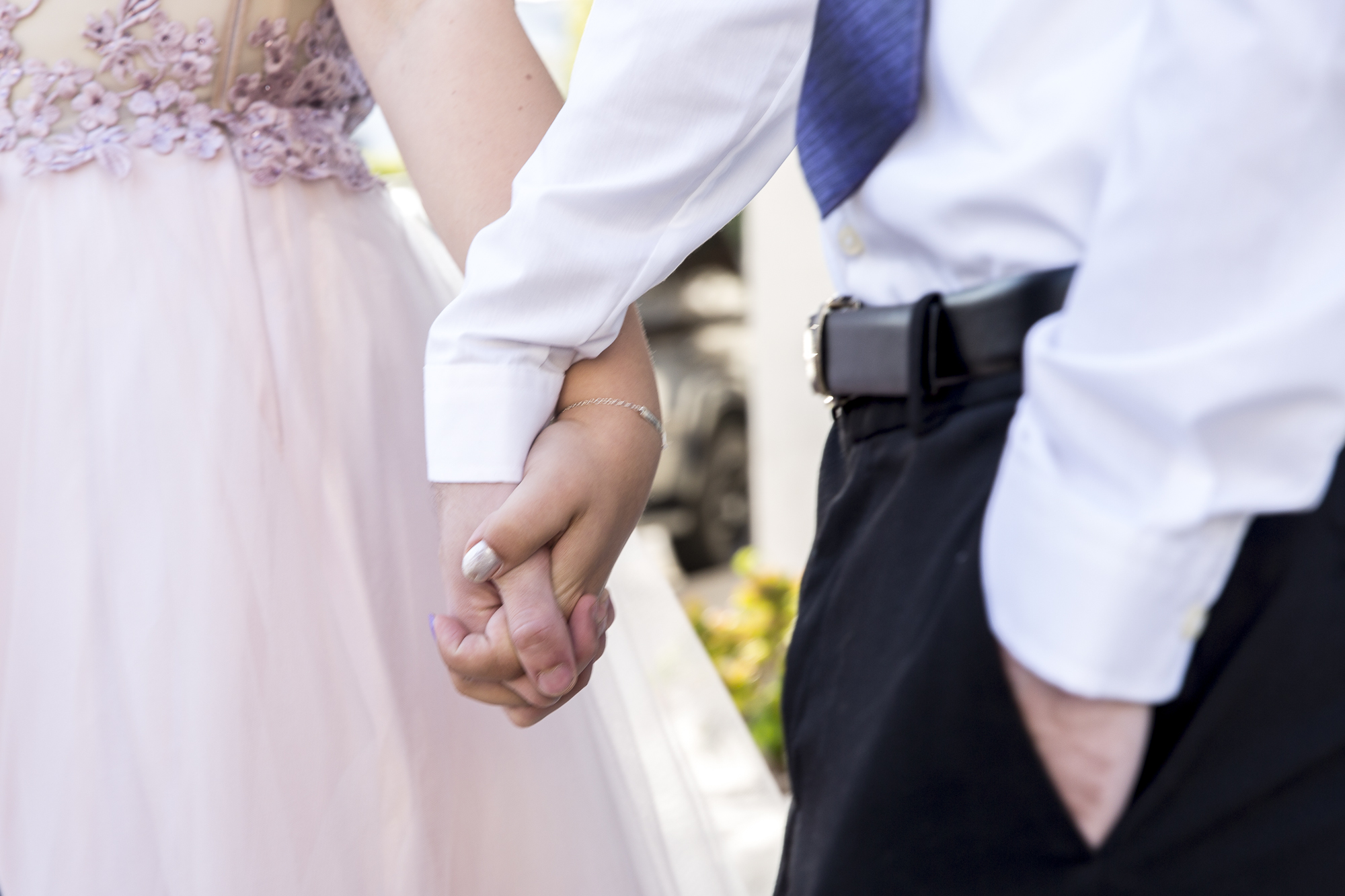 "Couple Amy Woodfine (left) and Tony Hokenson (right) hold hands outside the interfaith Church in Ocean Park in Santa Monica California on Friday May 18, 2018. The interfaith church has held ""Queer Proms"" in the past, but this year was the first that the prom's sponsor, Young People Creating Change (YPCC), partnered with the Princess Project Los Angeles (PPLA), Benefit Cosmetics, and Teen Vogue to produce the event. (Matthew Martin/Corsair Photo)"