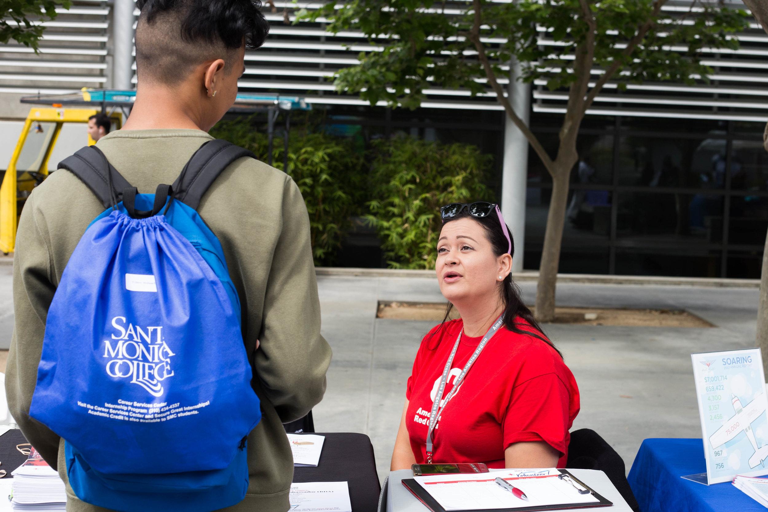Santa Monica College (SMC) Internship Fair: American Red Cross Table., Ana Ramirez, Volunteer Recruitment Representative talking to a SMC student.  SMC main campus. Santa Monica, California. Tuesday May 22. (Fernanda Rivera/ Corsair Photo)
