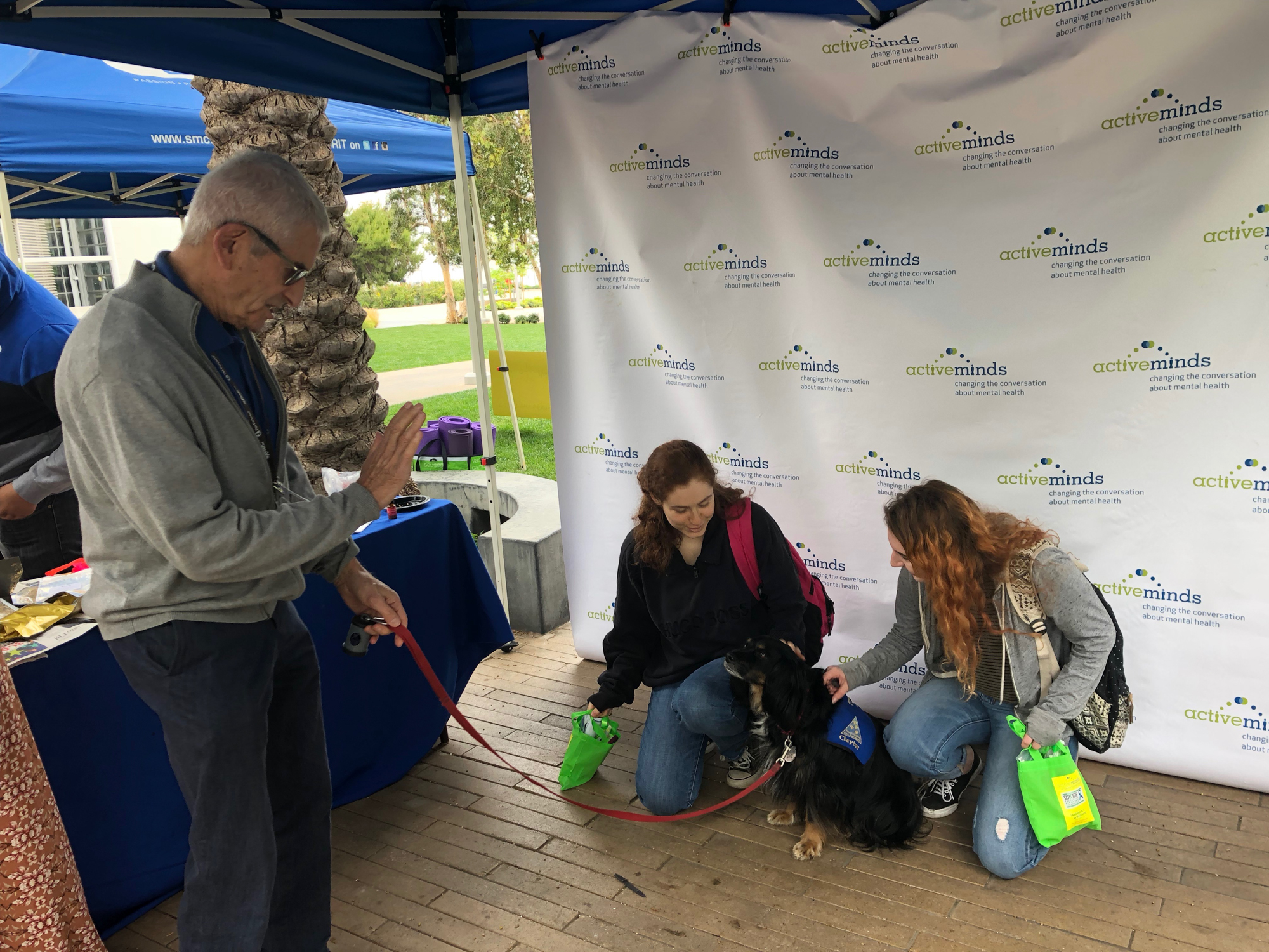 Bob Cowan with Paws for healing brought along dog Clayton to say hello at Active Minds event on Thursday May, 24 at Santa Monica College, in Santa Monica, California. Here with students Madeline Samson (left) and Skyler Stark (right). (Jennifer Nystrom/Corsair Photo)