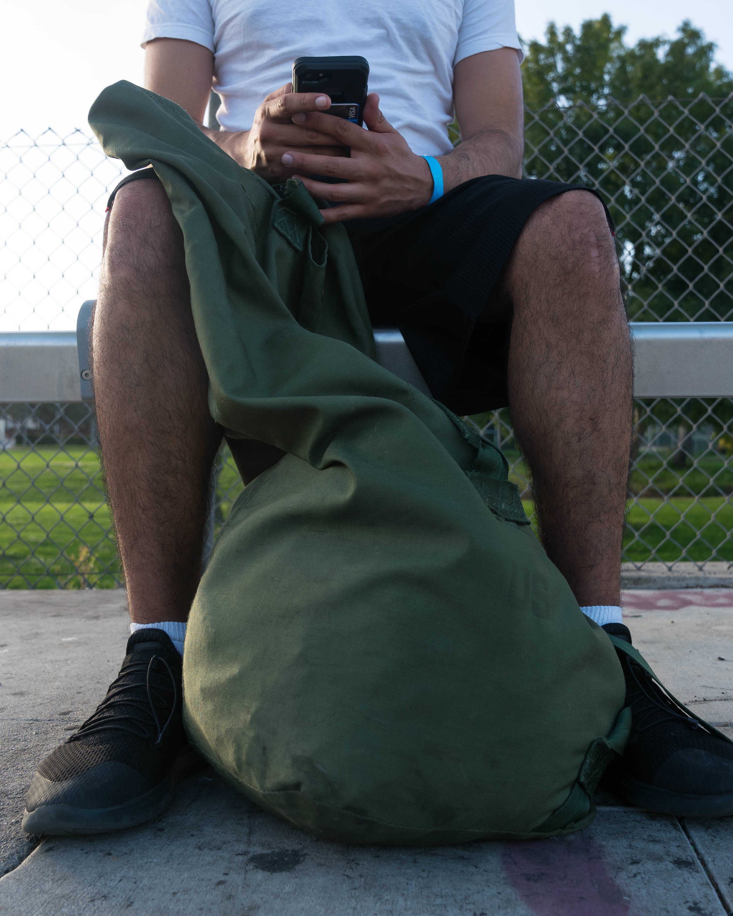 Santa Monica College student, Francisco Munoz, a veteran who experienced homelessness as an SMC student sits with his sea bag stuffed with a backpack, books, a jacket, and towel, at a bus stop in Los Angeles, California on June 3, 2018. Munoz, who cannot afford a car, says he takes the bus everywhere. (Helena Sung/Corsair Photo)