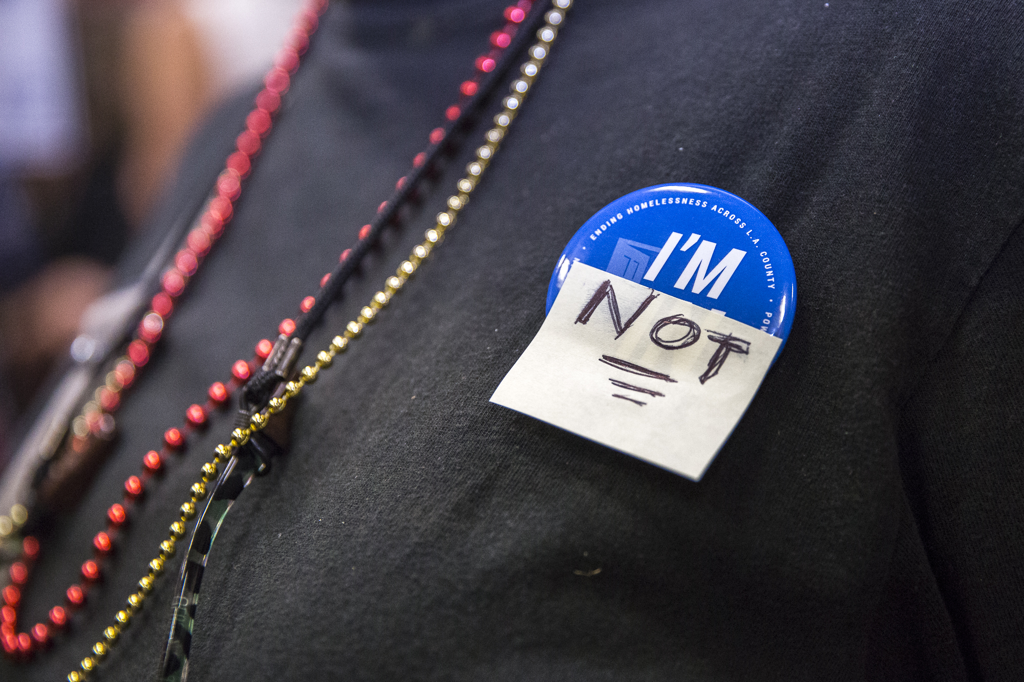 "A Venice local who is opposed to the building of a homeless shelter at the former metro bus lot at 100 E. Sunset in Venice that would house 100 people wear a button that reads, ""I'm Not"" during the town hall at Westminster Elementary School, in Venice, Calif on Wednesday, June 13 2018. (Photo by: Matthew Martin)"
