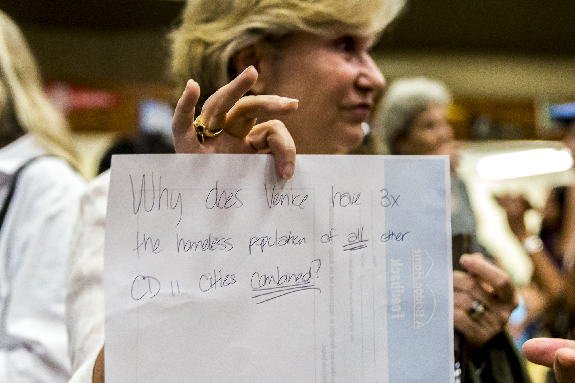 "Angelica Strong holds a piece of paper that asks, ""Why does Venice have 3x the homeless population than of all other CD II cities combined"" during the town hall discussing the building of a new homeless shelter in Venice that took place at Westminster Elementary School, in Venice, Calif on Wednesday, June 13 2018. (Photo by: Matthew Martin)"