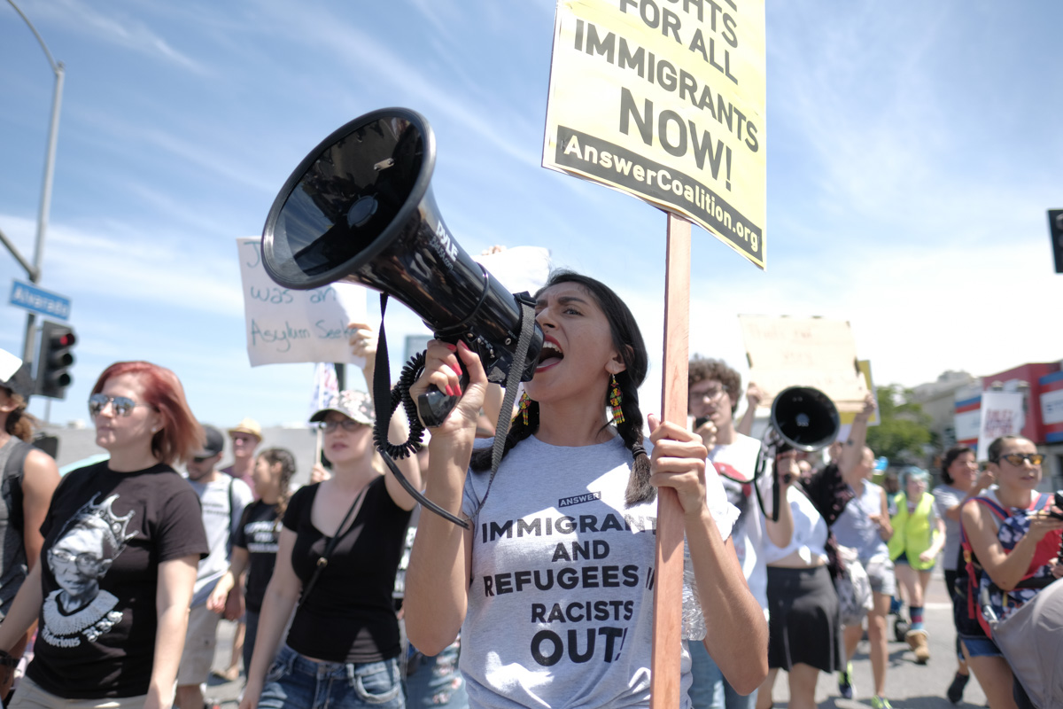Melina Rodriguez chants into a megaphone during the Families Belong Together March in Los Angeles, CA on July 21, 2018. (Photo by Jayrol San Jose)
