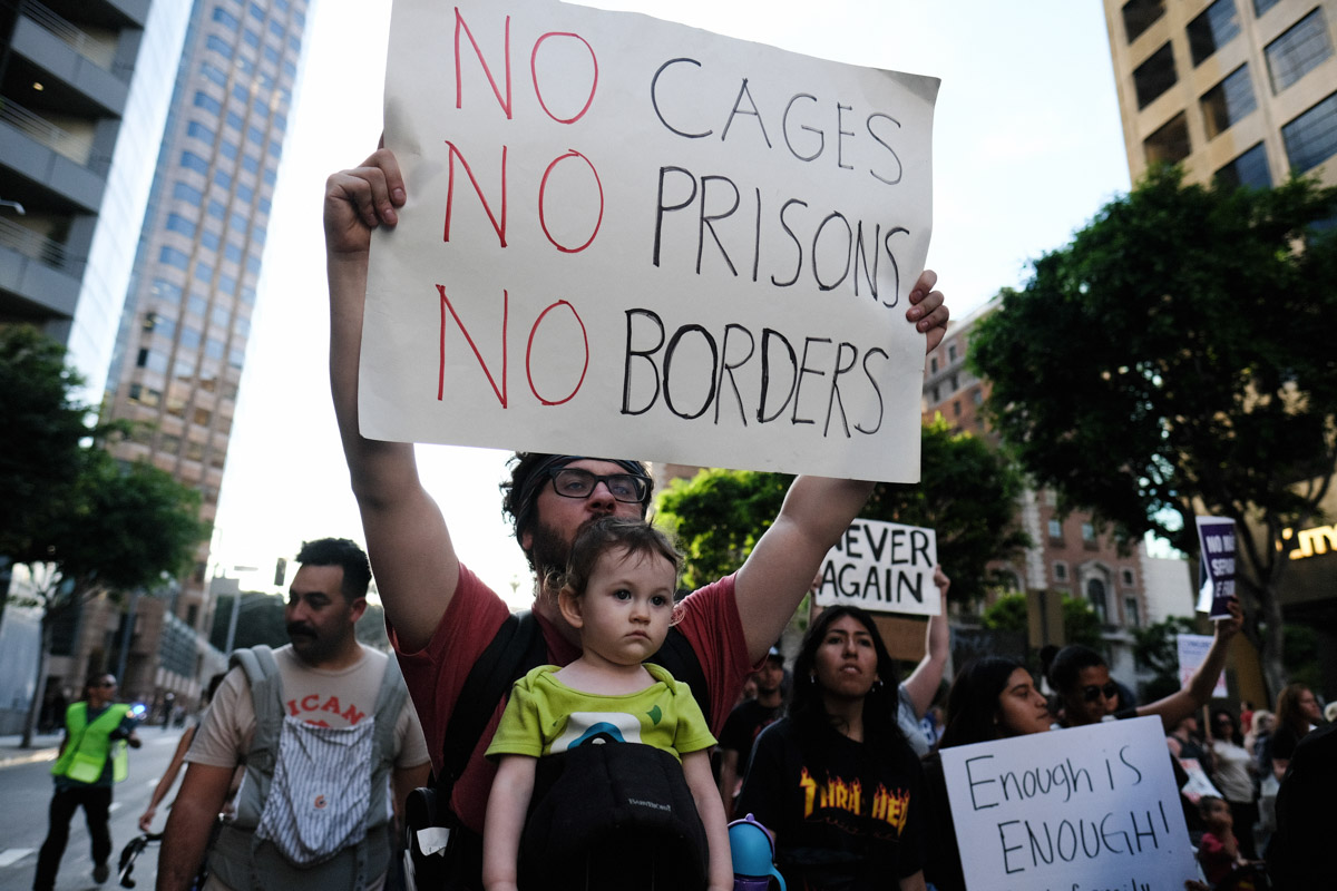 Protester holds a sign and carries his baby to protest against the family seperation in the United States in Los Angeles, CALIF on June 14, 2018.(Photo by Jayrol San Jose)