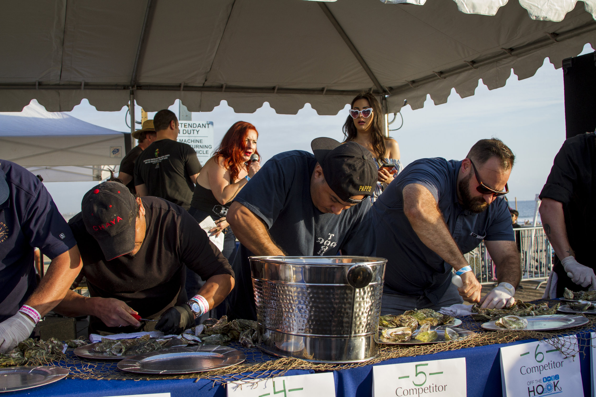 Competitors shucking oysters in under two minutes. At Off the Hook Seafood Festival. Oct. 6, 2018. By Yasser Marte.