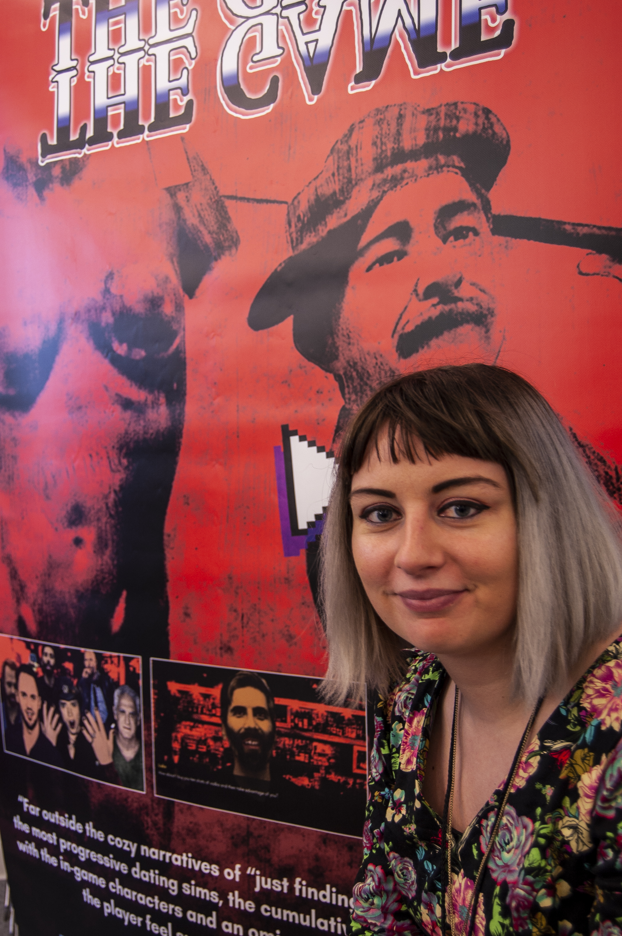 Developer/ designer Angela Washko poses with a poster of her gam