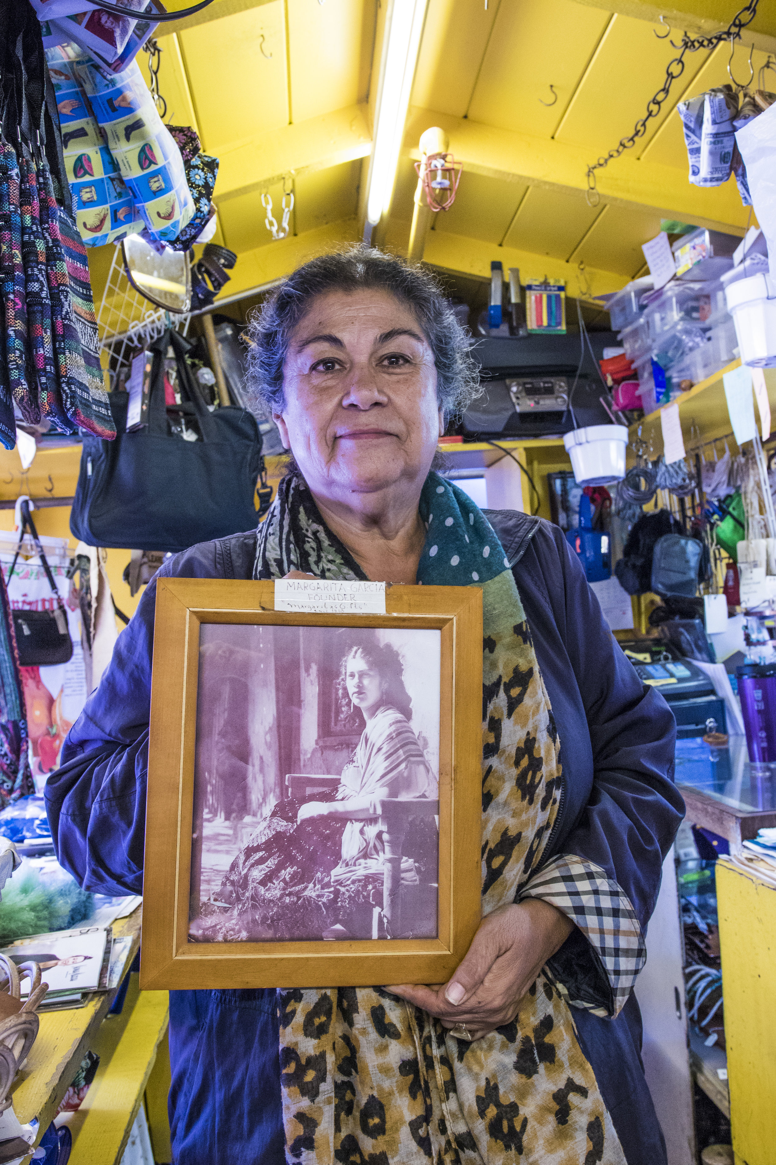 Emily Martinez, owner of Margartias, a shop on Olvera Street, holds a picture of her mother, Margarita Gomez. Their family is one of the seven original families to own shops on Olvera street after Margarita was given the store by Mrs. Sterling, the founder of Olvera Street. Emily says when she was a child in the 70s and 80s, the shop would be open until midnight everyday, with people trying to buy merchandise even as the store was closing. As of the last 7 years, business has slowed down tremendously. So much so that she now cannot afford to employ any workers and must run the shop and gather merchandise single handedly. (Zane Meyer-Thornton/Corsair Photo)