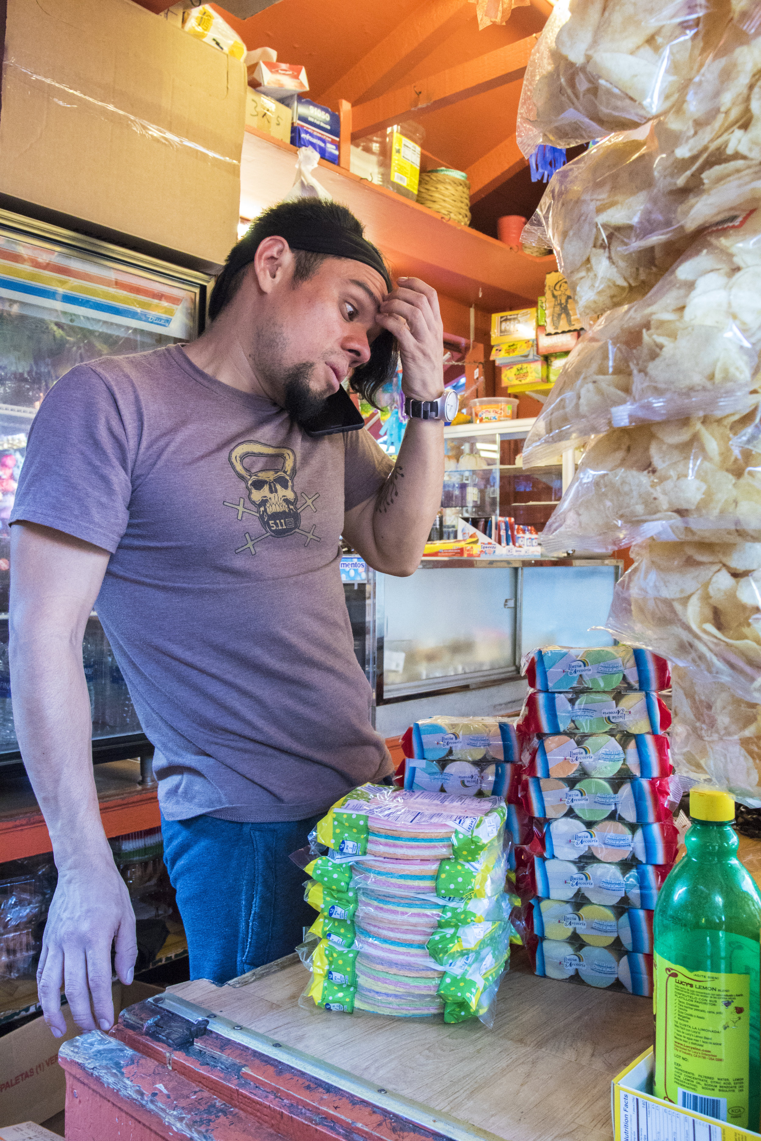 """Frank Franquis, an employee on Olvera Street, restocks his work space at Rudys Mexican Candy after an extremely busy weekend that he described as """"200-300%"""" more busy than usual, while taking a phone call from his boss where she told him that she would not be coming into work, on October 29, 2018. Although business booms during the Dia De Los Muertos celebration, most other times of the year are slow. Frank has been working at this shop for the last 3 years and works from 7 am to 8 pm everyday at both Rudys Mexican Candy and Munoz Mexican Store. Even in that short time has seen a dramatic decrease in customers. He believes it is due to the neighboring homeless population who often steal items from the shops. Although he is often a victim of theft, Franquis does not hold a grudge against the homeless. As he knows they are just doing what they need to do to get by. (Zane Meyer-Thornton/Corsair Photo)"""