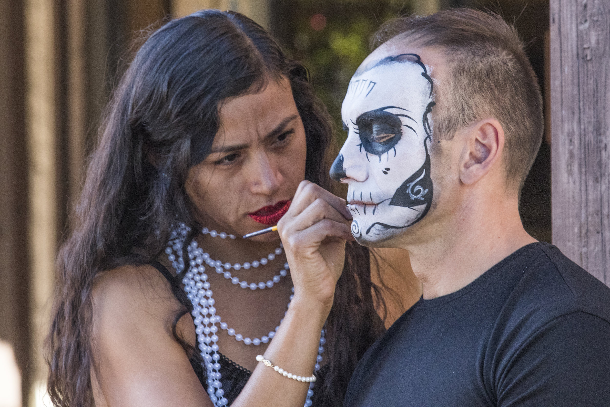 Carolina Hernandez (left) paints the face of one of her customers on October 31, 2018 at her face-painting booth on Olvera Street, in downton Los Angeles, California. Carolina is part of the 3rd generation of her family to work on Olvera Street. She says that business has been worse due to the homeless population and that the city council made a homeless shelter neighboring Olvera Street and did not notify any of the shop owners until it was already decided on. Her, and all the other shop owners had no say in the matter and no time to protest the decision. (Zane Meyer-Thornton/Corsair Photo)