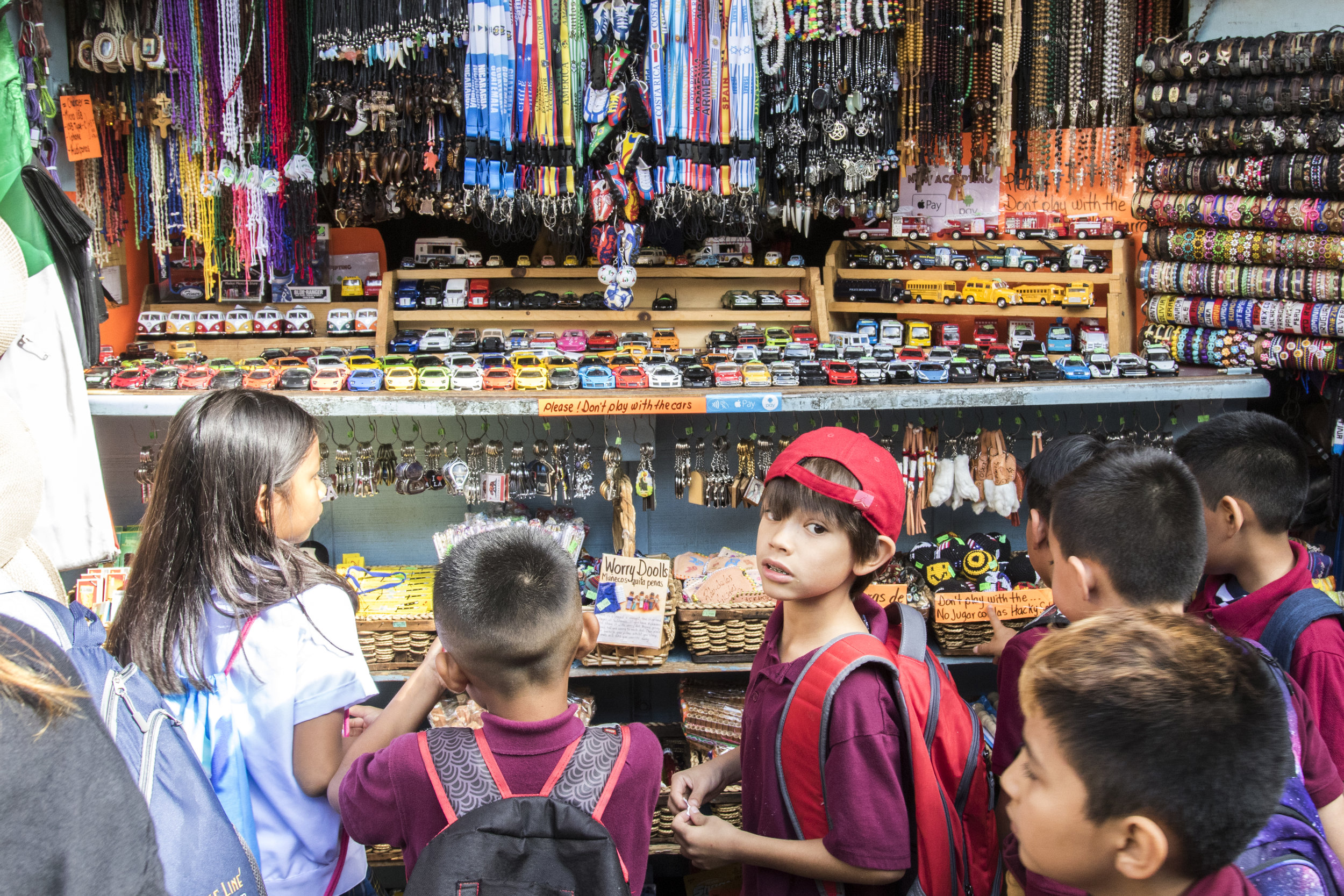 Children from the New Academy of Science and Art gather around Munoz Mexican Store, one of the many shops on Olvera Street during a school trip. Children are some of the most frequent buyers of goods on Olvera street. Most people just buy food and drinks, but children are consistently drawn into the colorful trinkets and accessories. According to shop owners, school tours are becoming less frequent due to inefficient funding. (Zane Meyer-Thornton/Corsair Photo)