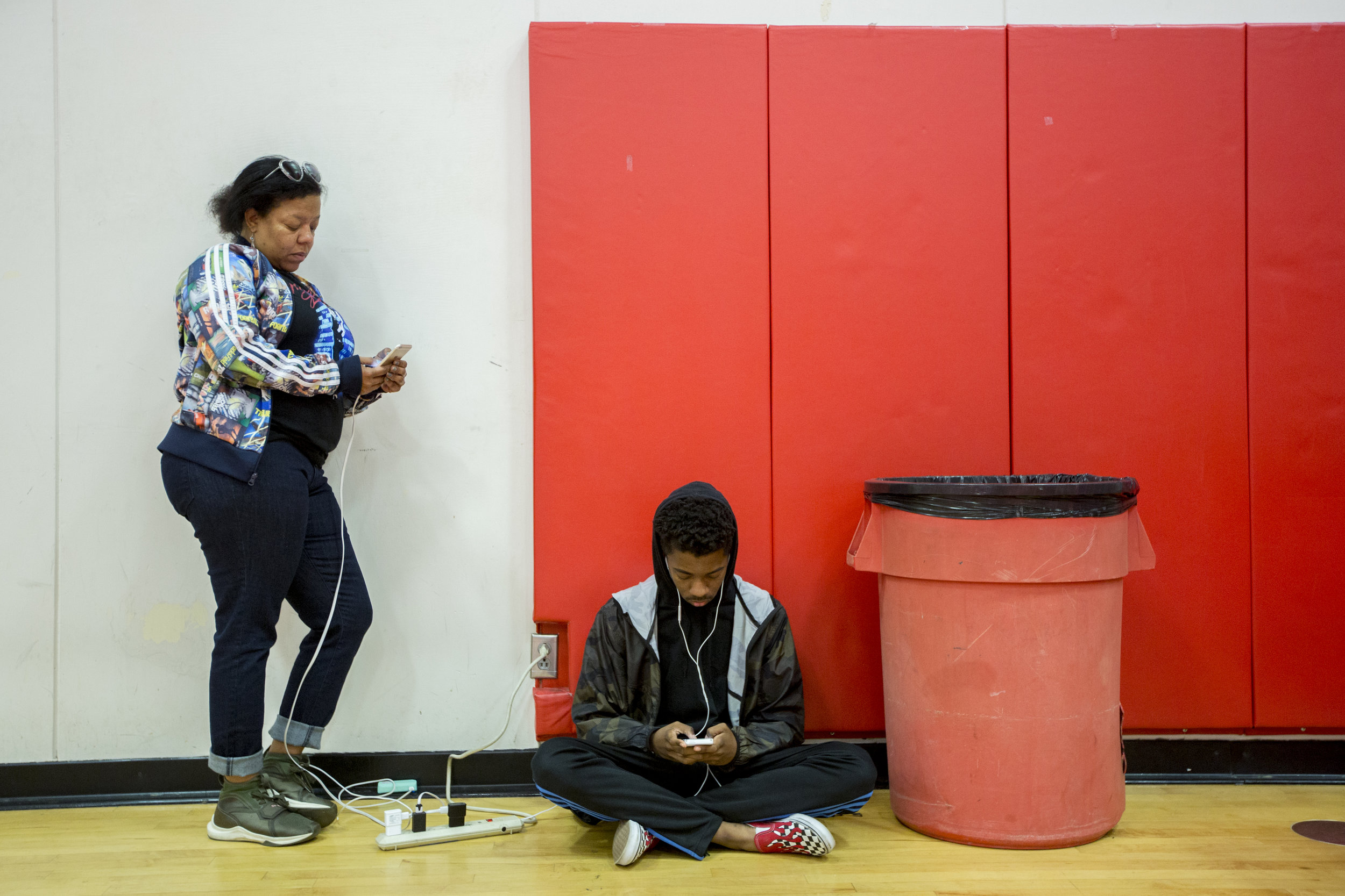 "Jenyce Johnson and her son, from Thousand Oaks, charge their phones and stay connected at the Woolsey fire evacuation center set up at Los Angeles Pierce College on November 9, 2018 in Woodland Hills, Calif. Already shaken by the Borderline Bar & Grill shooting that took place 5 blocks from where she lives and as a student at Moorpark College who is in the middle of studying for exams, Johnson admitted that she was not tuned in to how close the fire was to her home until she was notified by a friend around 1 a.m. to evacuate. As she opened her door to go pack up the car to evacuate, Johnson said, ""All you could see was red from the fire and then you could actually see the fire coming down, crawling down, the hill."" While Johnson appeared to be handling things well, she shared that both tragedies are psychologically heavy to deal with and too much to carry all at once. Johnson said, ""One tragedy and then another tragedy in the same area is a lot. I thought it was the third safest, quote unquote, city in America, but you know even in the safest places in America ill things can occur."" The last time she checked-in her area was still under a mandatory evacuation, but she has no idea if her home is safe. (Jose Lopez)"