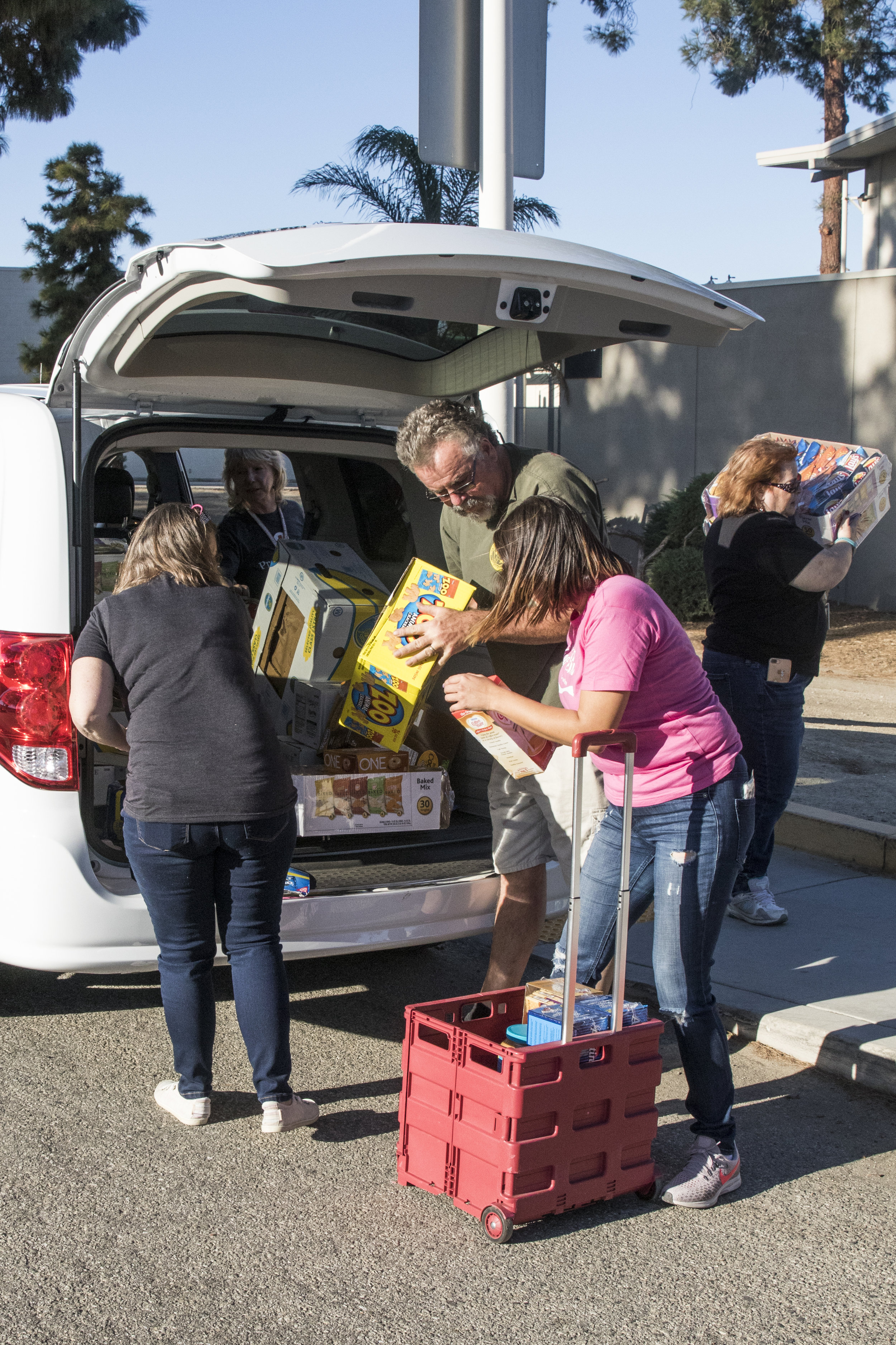 Pierce College employees and volunteers unload a car full of resources for evacuees of the Woolsey Fire who have taken refuge at Pierce College in Woodland HIlls, California on November 9, 2018. (Zane Meyer-Thornton/Corsair Photo)