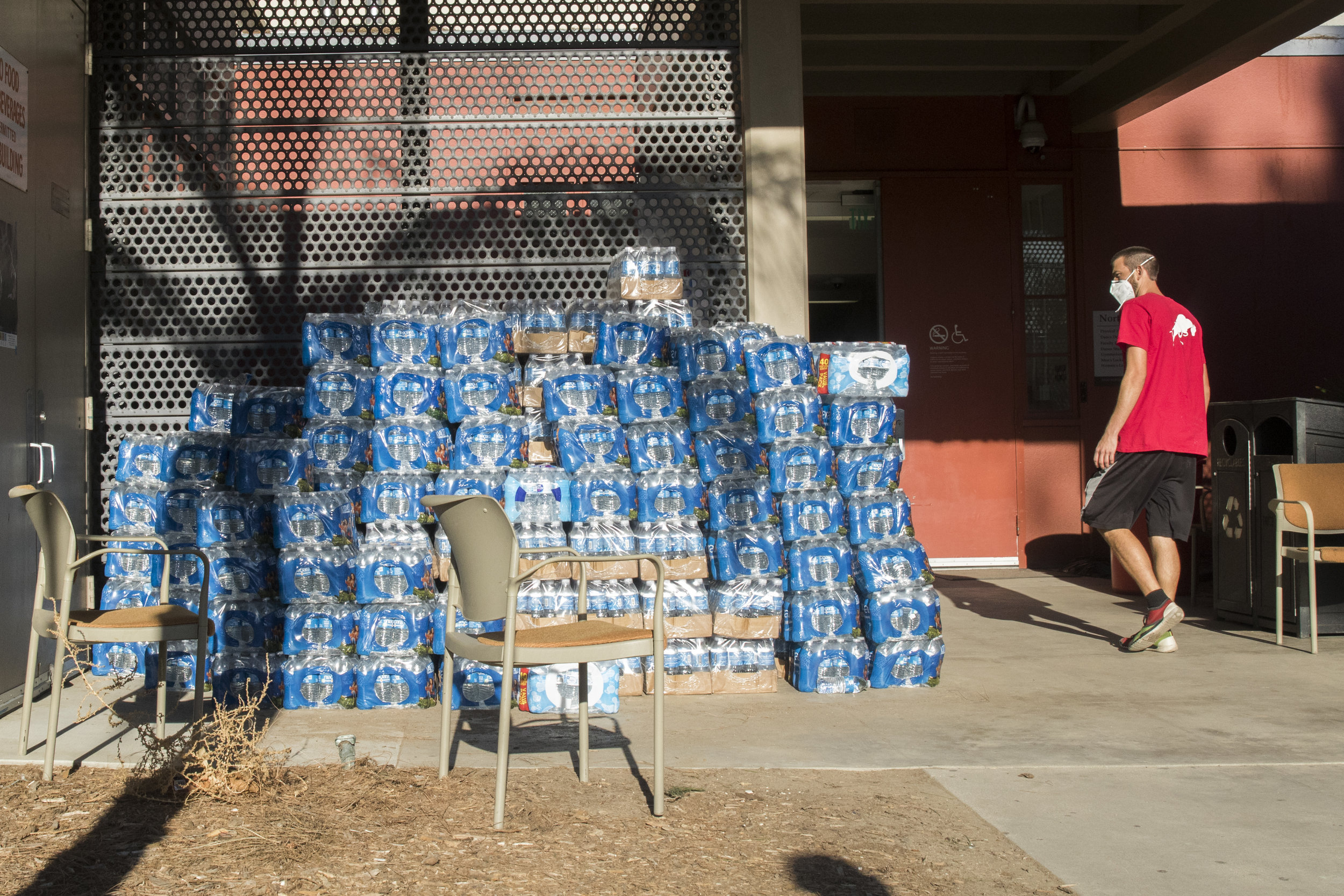 A volunteer walks by water bottles donated by Juan Mutaz (not pictured), a store manager for a Home Depot located in West Hills, California. The water bottles are readily available for any evacuee of the Woolsey Fire who have taken refuge at Pierce College in Woodland Hills, California on November 9, 2018. (Zane Meyer-Thornton/Corsair Photo)