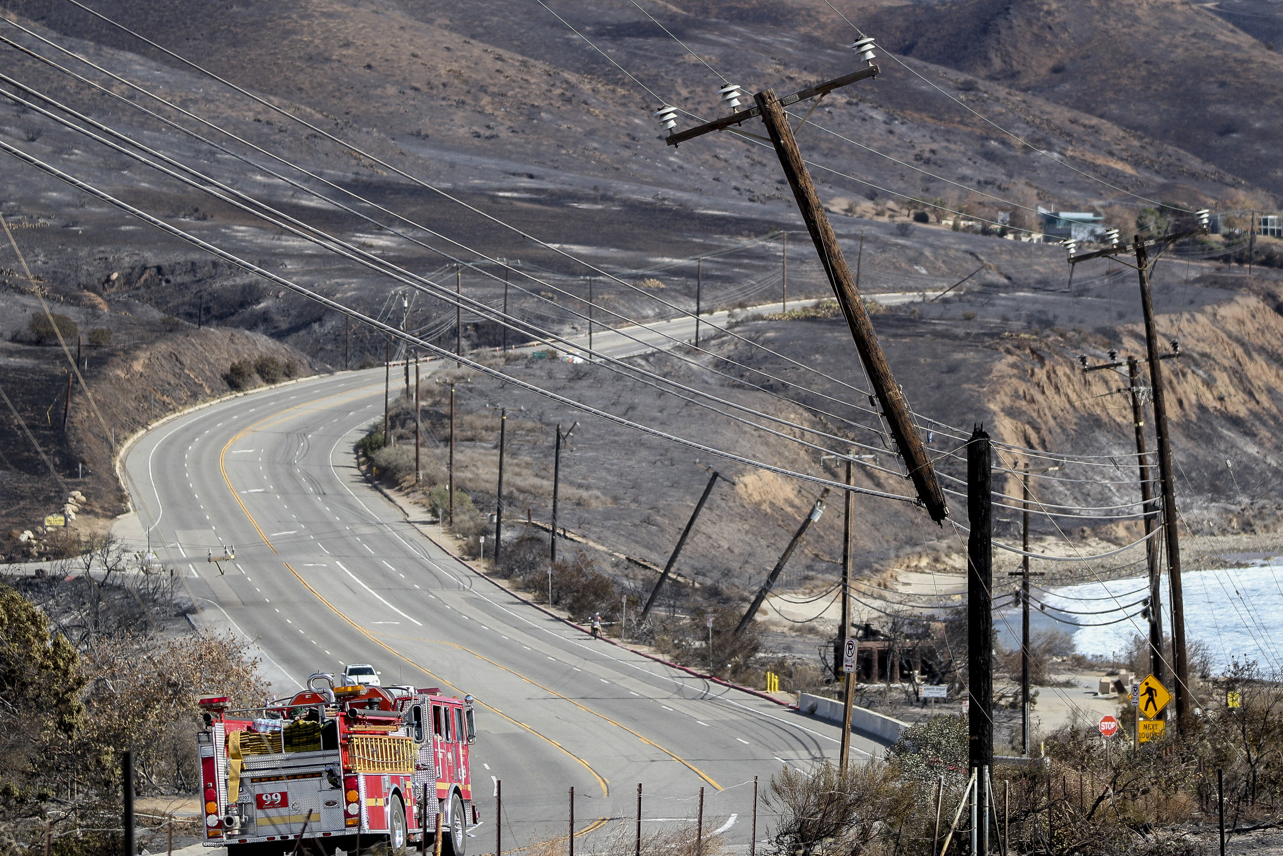 A fire truck drives by an electric pole damaged by the Woolsey fire along Pacific Coast Highway near Leo Carillo State Park on November 13, 2018 in Malibu, Calif. (Jose Lopez)