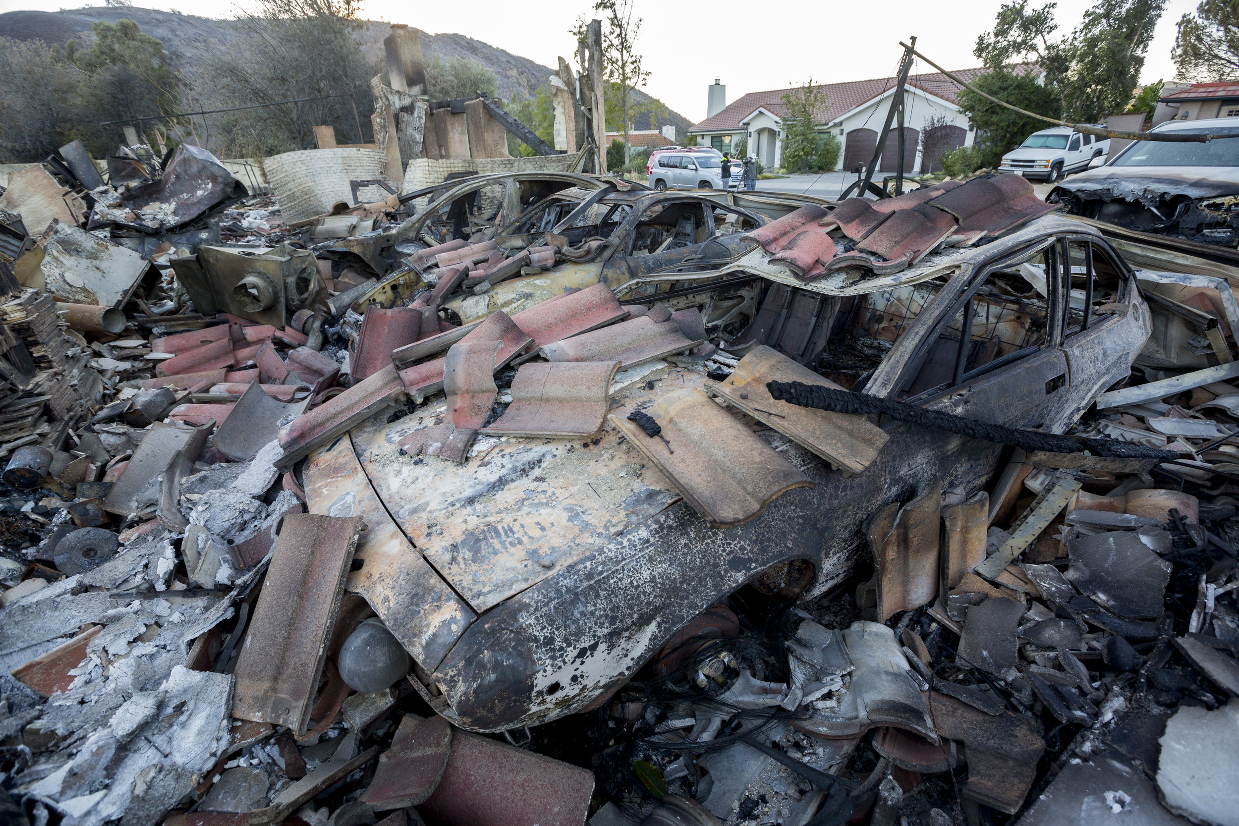 Cars burned out by the Woolsey fire sit under the rubble of a garage along Flintlock Lane on November 12, 2018 in the Bell Canyon neighborhood of West Hills, Calif. (Jose Lopez)