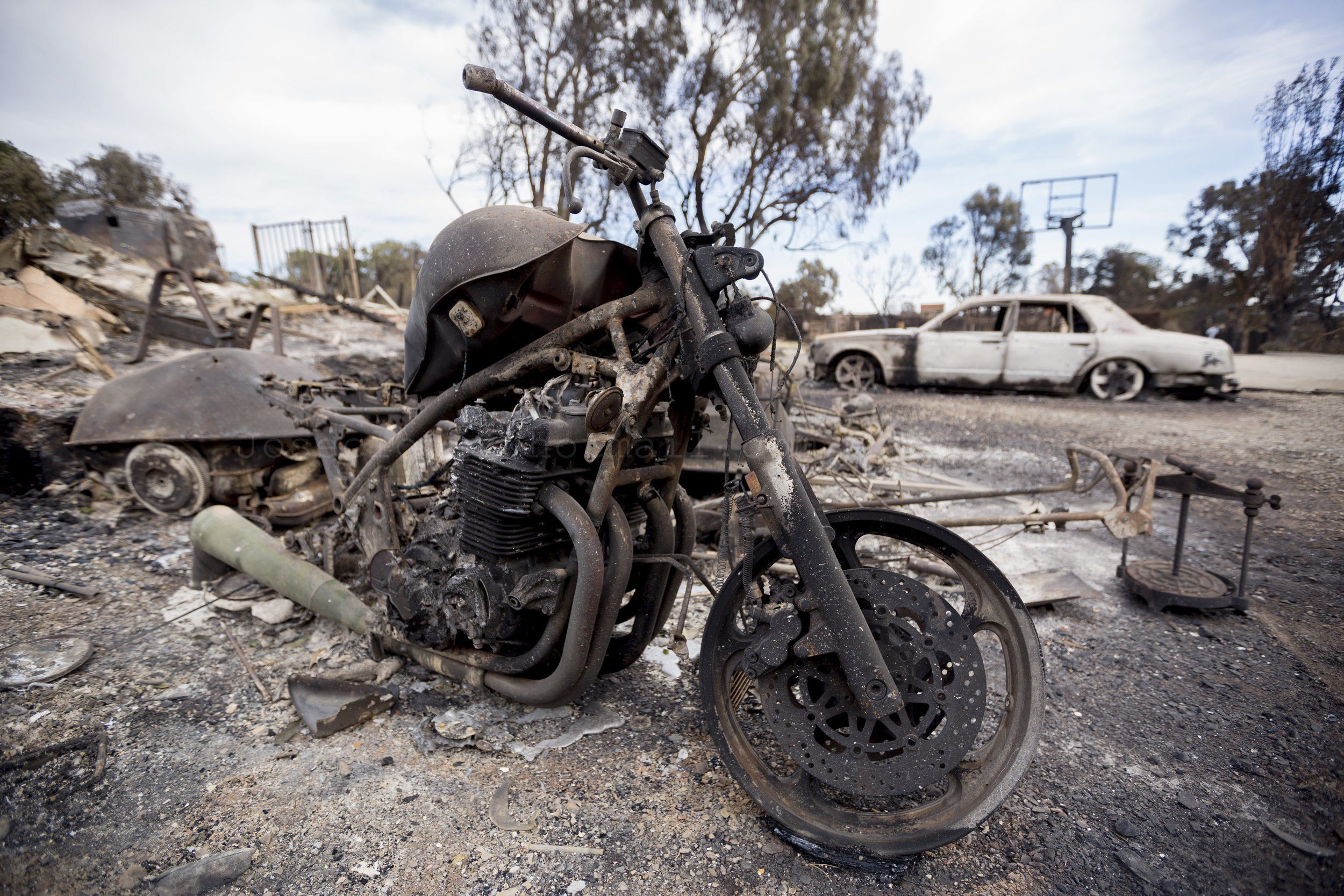 A motorcycle and car sit burned out by the Woolsey fire at a home along Harvester Road on November 14, 2018 in Malibu, Calif. (Jose Lopez)
