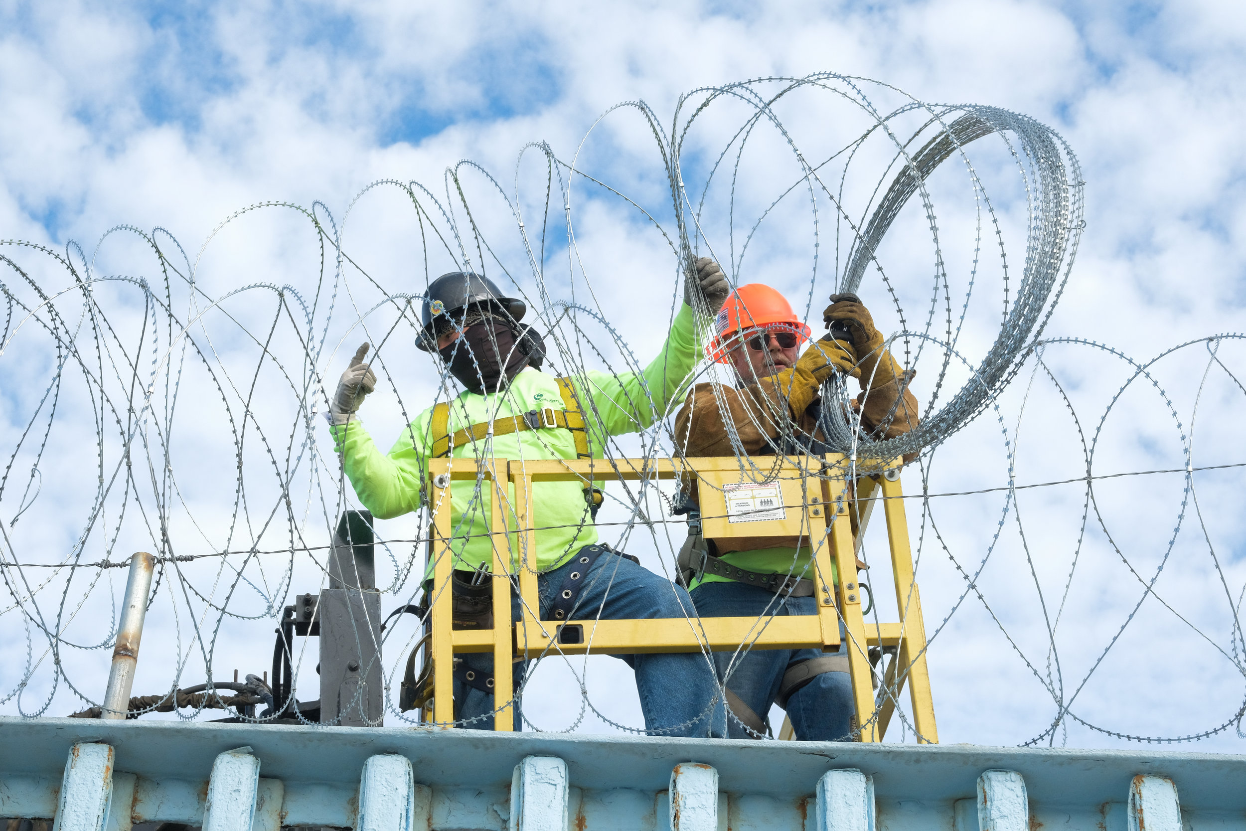 Construction workers on the United States side of the wall place Barbed Wire on top of the Border Wall fence in Friendship Park in Tijuana, Mexico on November 16, 2018. (Photo by Jayrol San Jose)