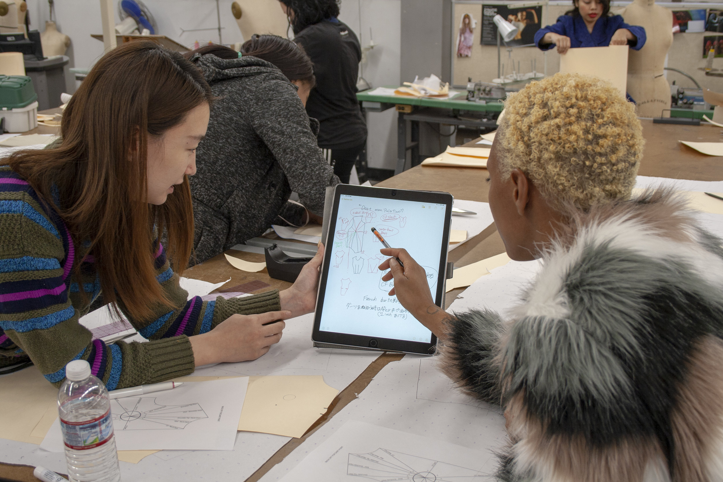 On Feburary 22, 2019 within the Fashion Department in Santa Monica College (SMC) where Porscha Woodard learns, and works on the basics of tracing. Professor Sofi Khachmanyan teaches the class Fashion 6A, where she helps the students on a very close level. Kyoka Takahashi, classmate of Porscha helps her understand how the design is to be made by showing her persoanl notes.