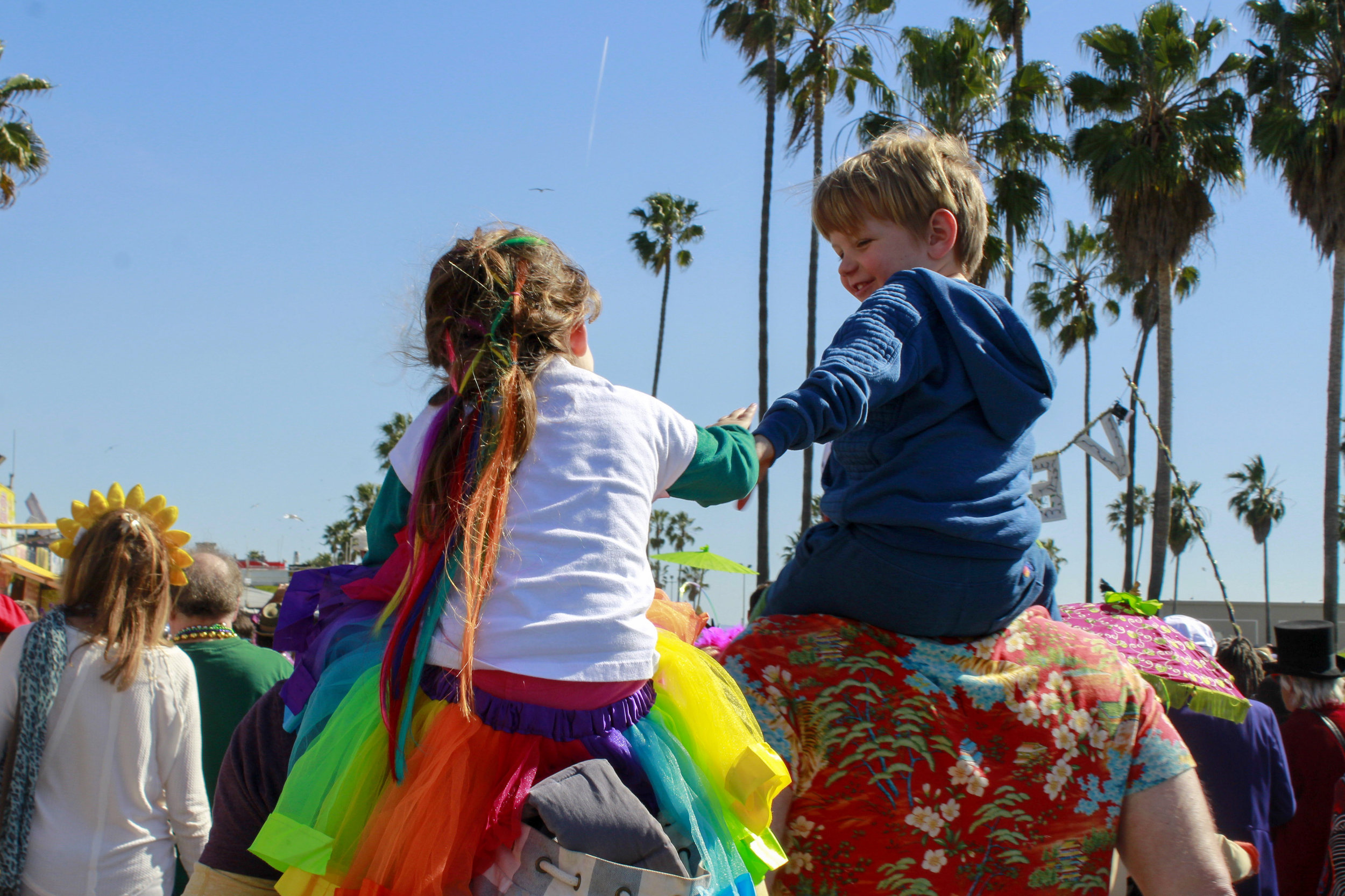 Children reach for one another as they rest on shoulders amongst the chaos of the 17th annual Venice Beach Mardi Gras parade on Feb 23, 2019 in Los Angeles, California. Photo by Danica Creahan.