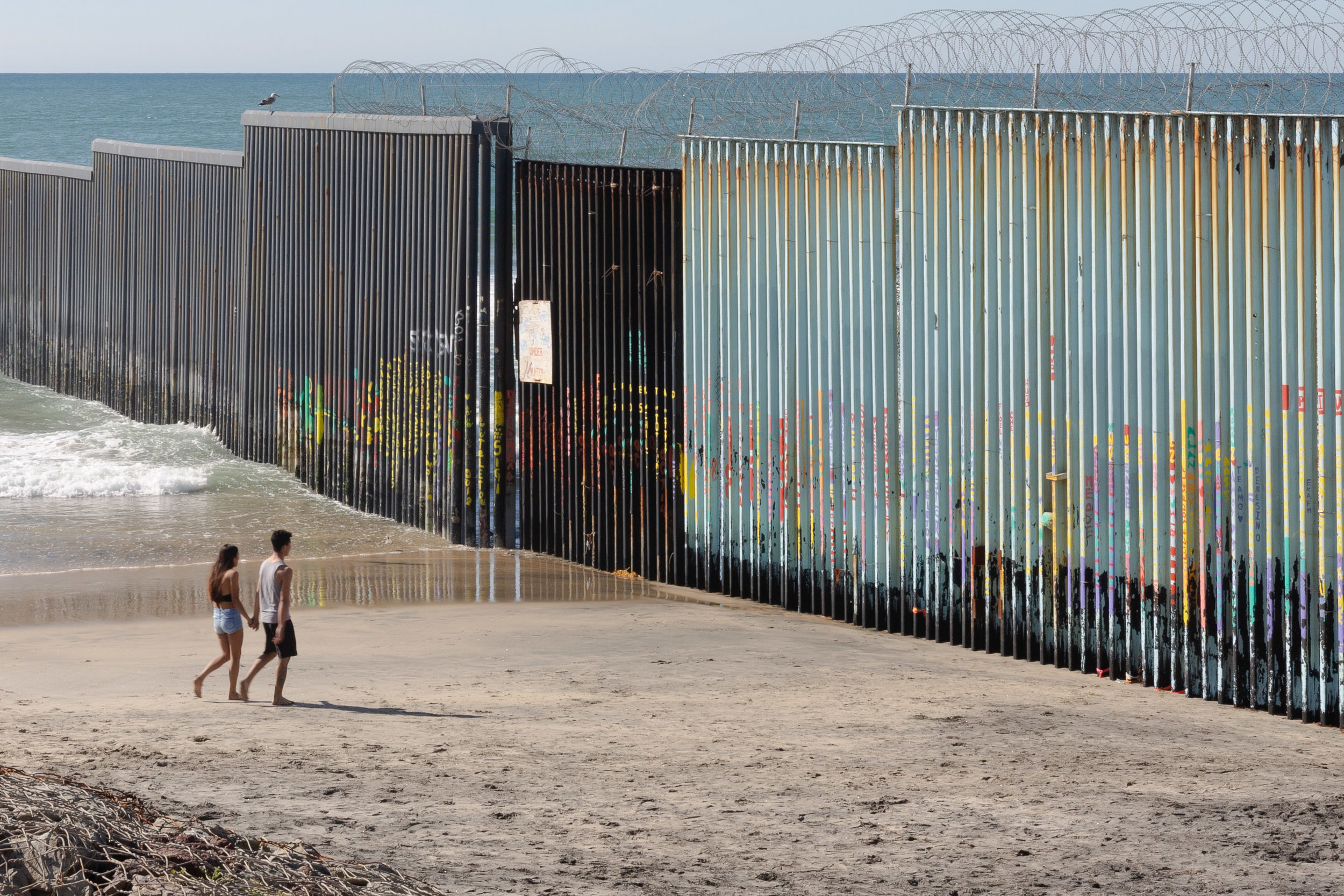 A couple walks along the beach close to the US-Mexican border wall in Playas de Tijuana in Tijuana, Mexico, on Saturday, February 23, 2018. Photo by: Ben Camacho.