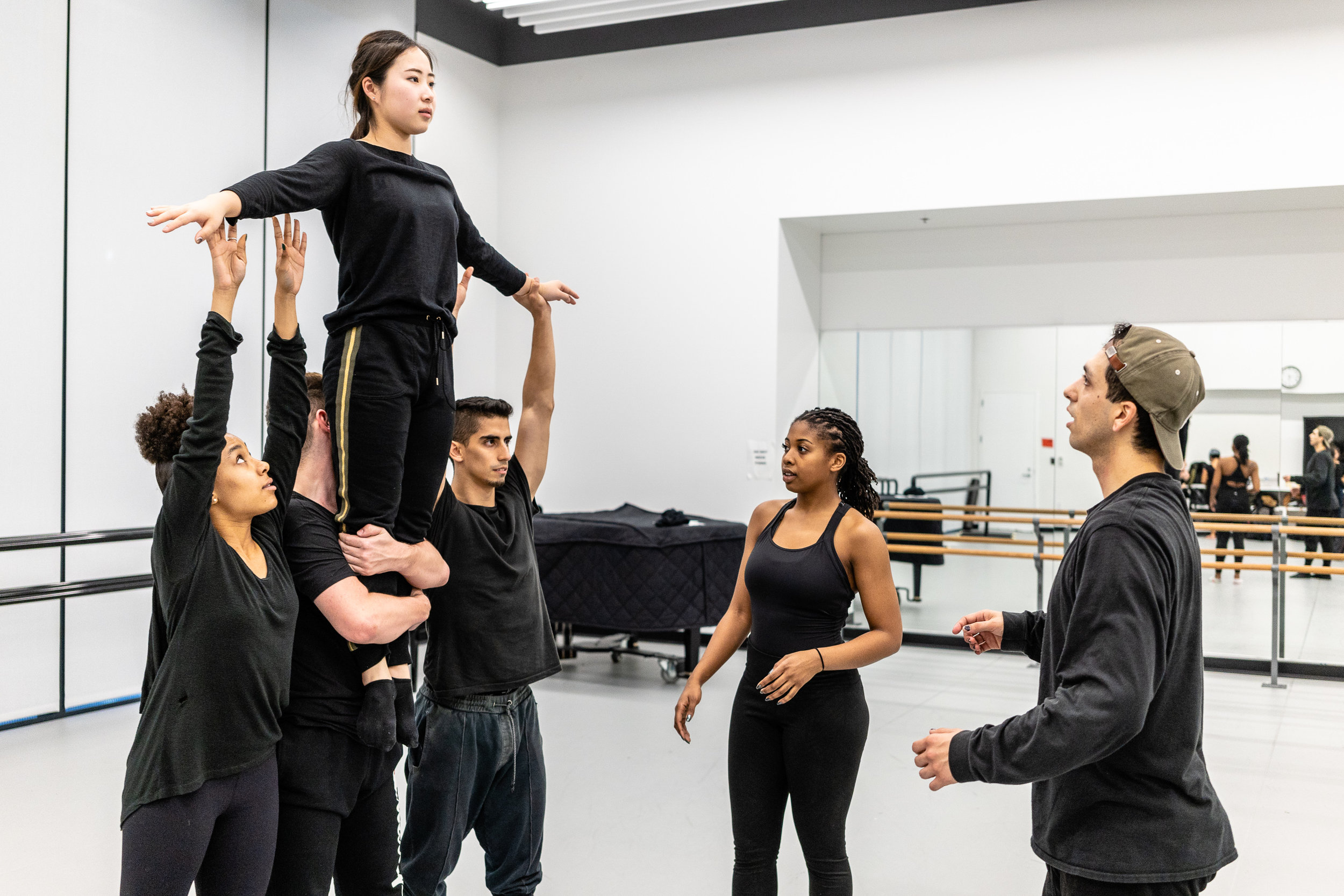 SMC dance majors hold Yurino Niyama aloft as student choreographer Erik Fine (in baseball cap) adjusts their movement in SMC's Core Performance Center on Tuesday, Feb. 26, 2019. Fine is rehearsing his new work, titled by the number seven in tally marks, which will premiere at Synapse Dance Theater at the Broad Stage at SMC's Performing Arts Center campus on Friday and Saturday, May 24 and 25. (Glenn Zucman/The Corsair)