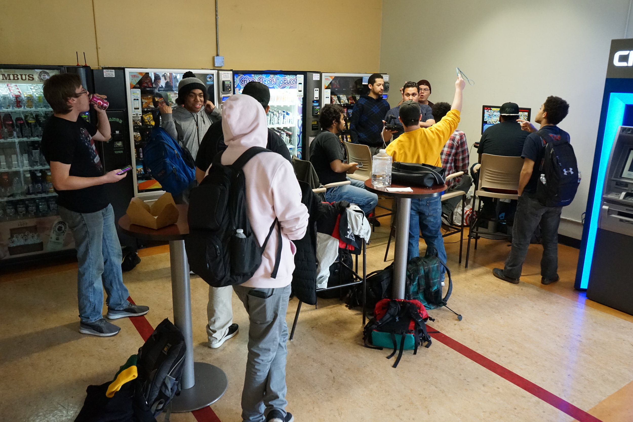 A crowd of SMC students gathers around the gaming setup at the back of the Main Campus cafeteria, Monday, March 4, 2019, at Santa Monica College in Santa Monica, Calif. Despite their regular meet-ups, the restrictions and qualifications for forming a club have kept the group from forming an official Gaming Club through the college. (The Corsair/Nicole Haun)