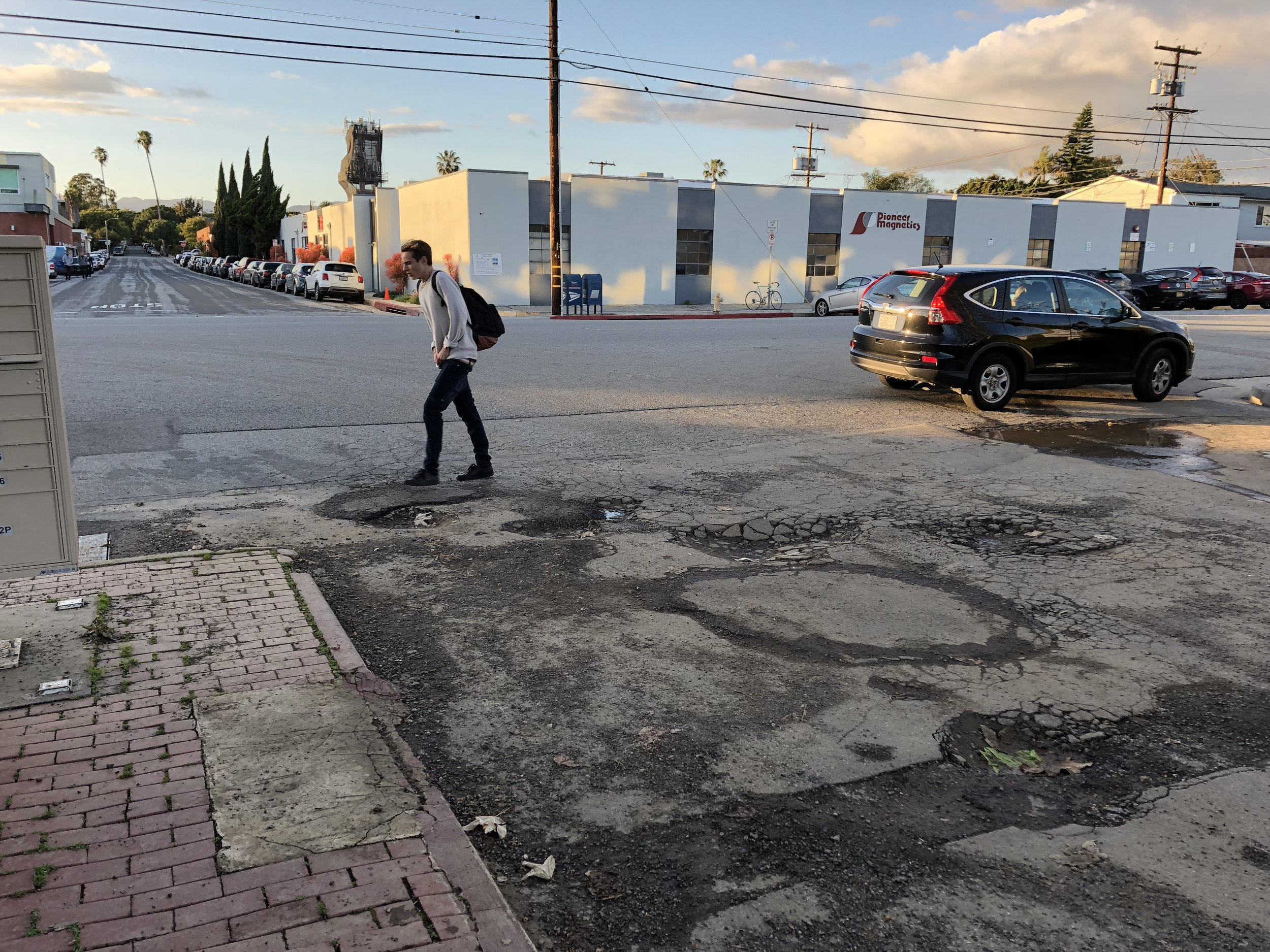 A pedestrian walks around a group of potholes at the intersection of Nebraska Ave and Berkeley St in Santa Monica on March 7, 2019. Santa Monica, California. Michael Fanelli / The Corsair.