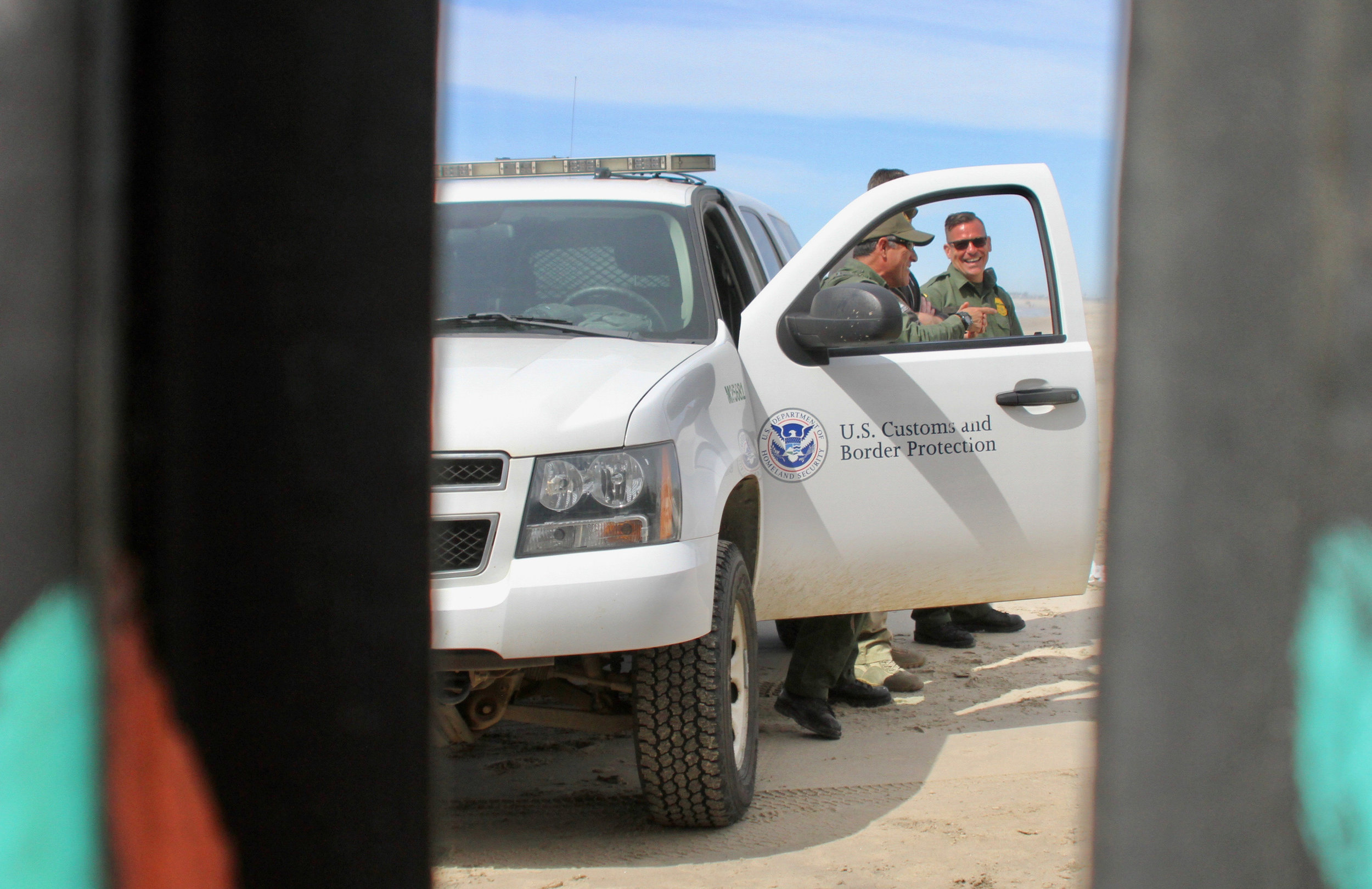 Three Border Patrol agents laughing and standing by a patrol car as construction along the border wall in Playas De Tijuana took place in Playas de Tijuana on Friday, March 15, 2019 in Tijuana, Mexico. The construction on this section of the border wall comes after two different incidents of significantly large groups of migrants crossing through the border wall between gaps and openings on Thursday, March 14 and on Friday, March 15.( Ryanne Mena / The Corsair )