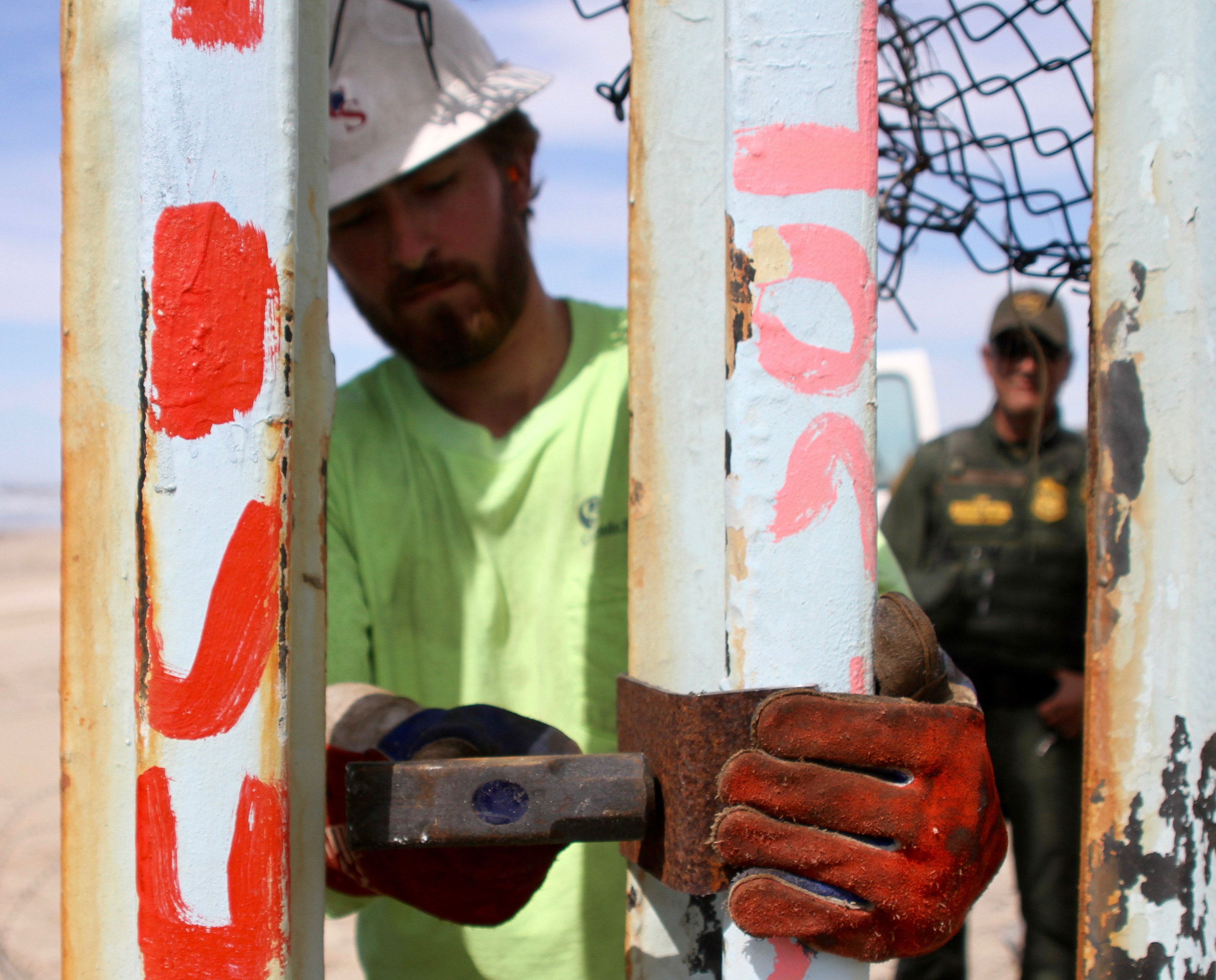 "A Cerrudo Services construction worker hammers a piece of rusted steel onto the border wall in Playas de Tijuana while a Border Patrol agent watches on standby on Friday, March 15, 2019 in Tijuana, Mexico. Cerrudo Services is a ""construction and service contractor specializing in federal government contracting,"" according to the company's website. The construction on this section of the border wall comes after two different incidents of significantly large groups of migrants crossing through the border wall between gaps and openings on Thursday, March 14 and on Friday, March 15. ( Ryanne Mena / The Corsair )"
