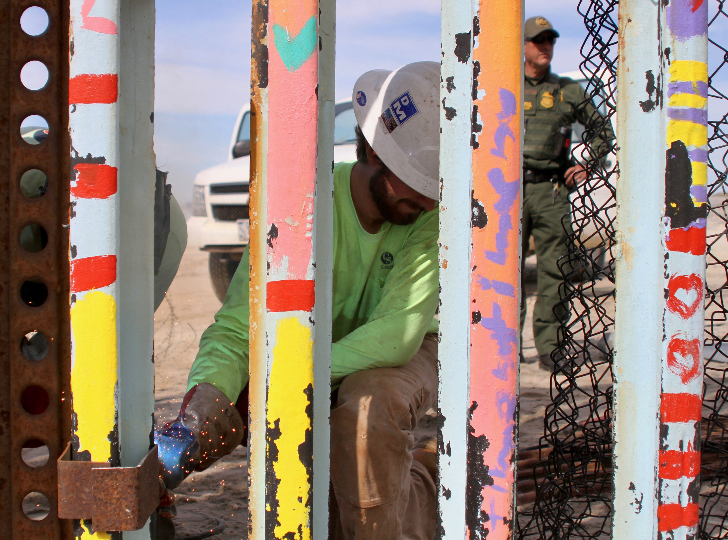 "A Cerrudo Services construction worker welds a piece of rusted steel onto the border wall in Playas de Tijuana as a Border Patrol agent watches on standby on Friday, March 15, 2019 in Tijuana, Mexico. Cerrudo Services is a ""construction and service contractor specializing in federal government contracting,"" according to the company's website. The construction on this section of the border wall comes after two different incidents of significantly large groups of migrants crossing through the border wall between gaps and openings on Thursday, March 14 and on Friday, March 15. ( Ryanne Mena / The Corsair )"