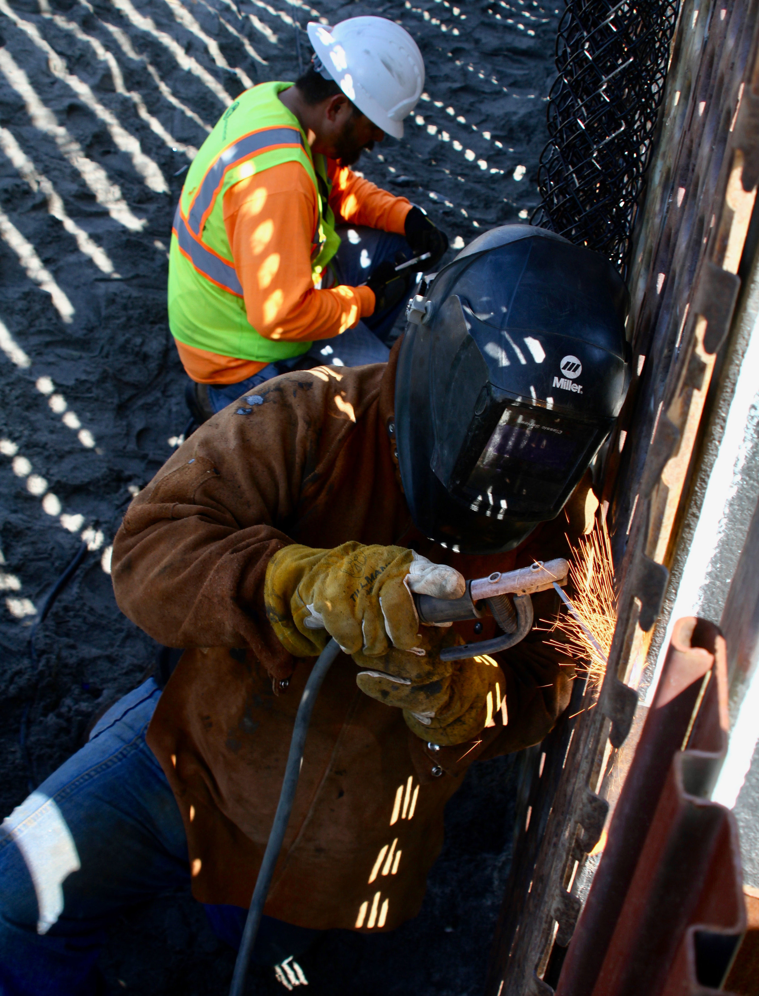 "A masked Cerrudo Services construction worker welding a piece of rusted steel onto the border wall in Playas de Tijuana while another worker prepares to also continue the second day of construction along the wall on Saturday, March 16, 2019 in Tijuana, Mexico. Cerrudo Services is a ""construction and service contractor specializing in federal government contracting,"" according to the company's website. The construction on this section of the border wall comes after two different incidents of significantly large groups of migrants crossing through the border wall between gaps and openings on Thursday, March 14 and on Friday, March 15.( Ryanne Mena / The Corsair )"