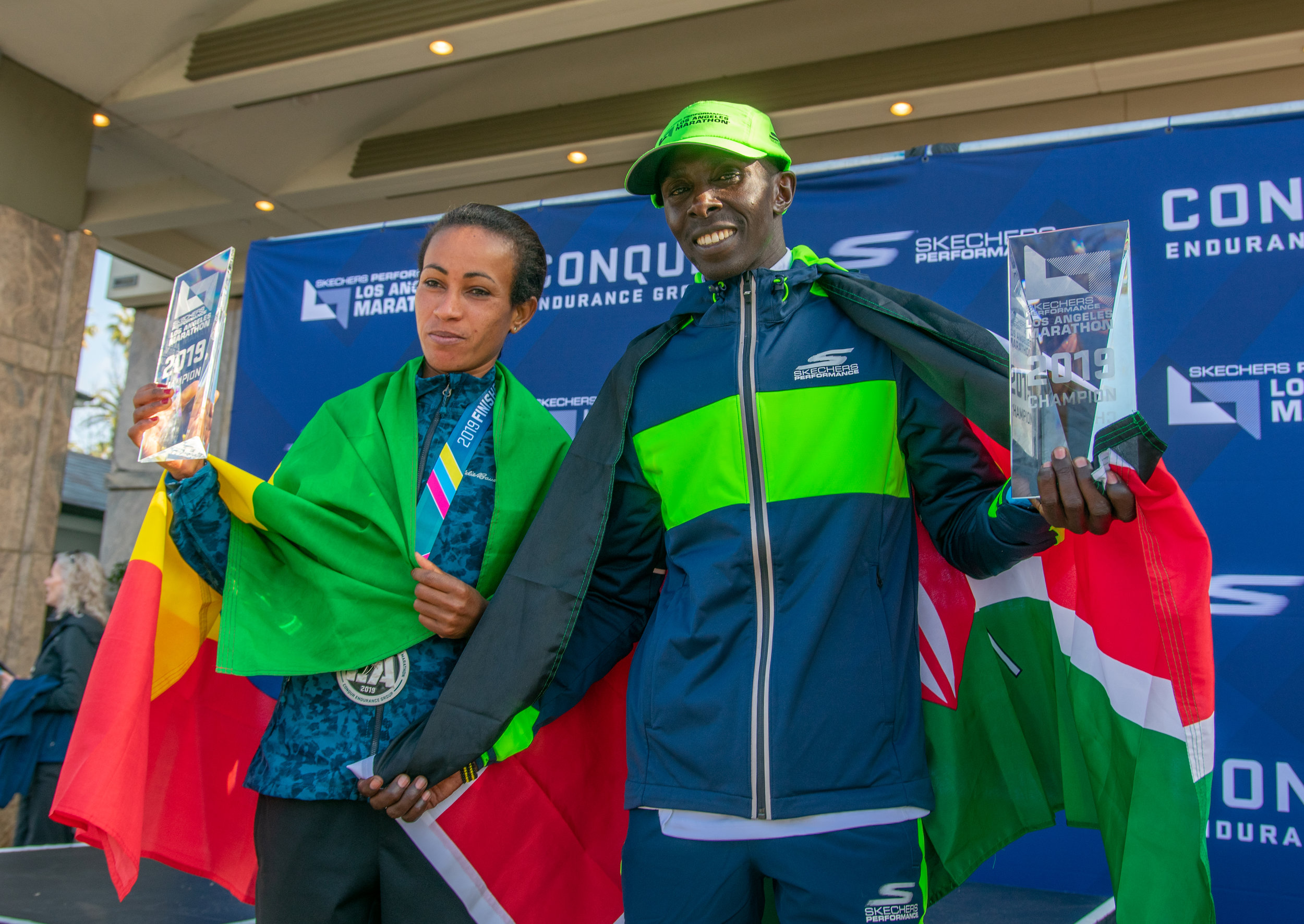 The winners of the Women's and Men's leaderboards, (left to right) Askale Merachi of Ethiopian and Elisha Barno of Kenya pose with their medals and trophies in front of the Fairmont Hotel in Santa Monica Calif. on Sunday March 24th 2019. (Conner Savage Corsair Staff).