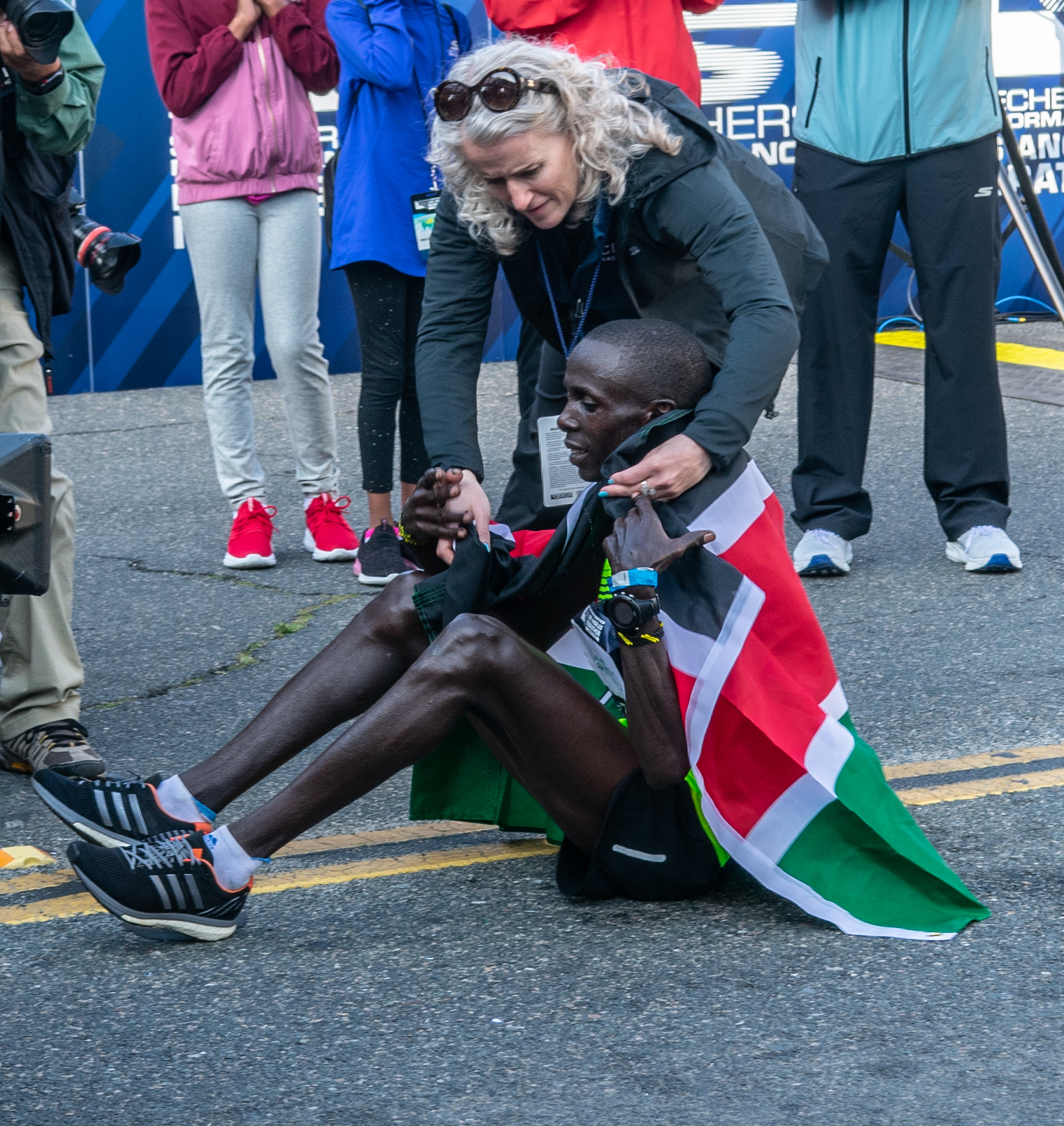 Tracey Russell, CEO of Conqur Endurance Group, placing the Kenyan flag on Los Angeles Marathon winner Elisha Barno as he is resting on Ocean Ave, on Sunday March 24th 2019, in Santa Monica Calif. (Conner Savage Corsair Staff).