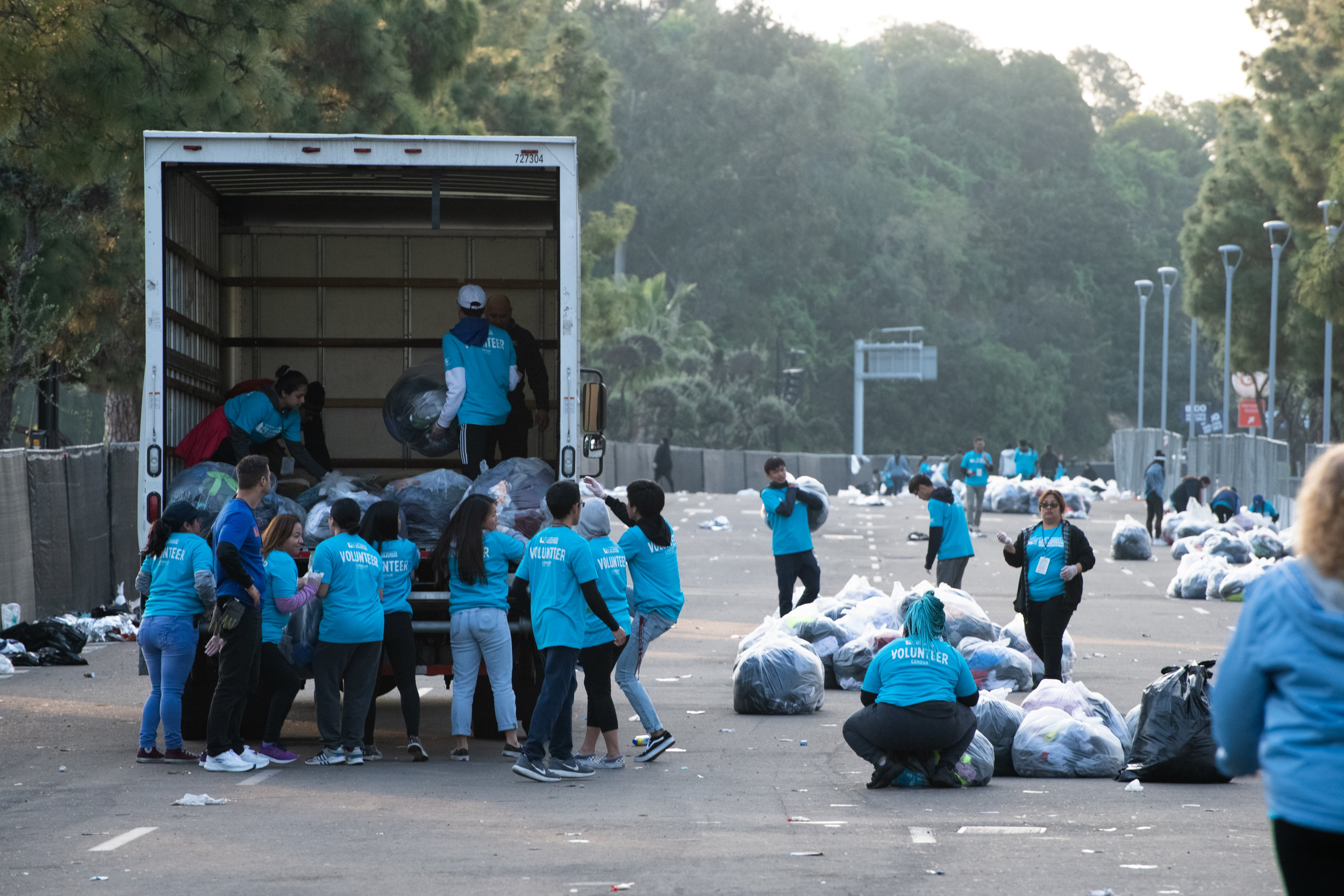 Volunteers for the 34th Los Angeles Marathon gather up items of clothing thrown off by participants near the starting line, Sunday morning, March 24, 2019, at Dodger Stadium in Los Angeles, Calif. The items are put into large bags that are then donated to Goodwill.