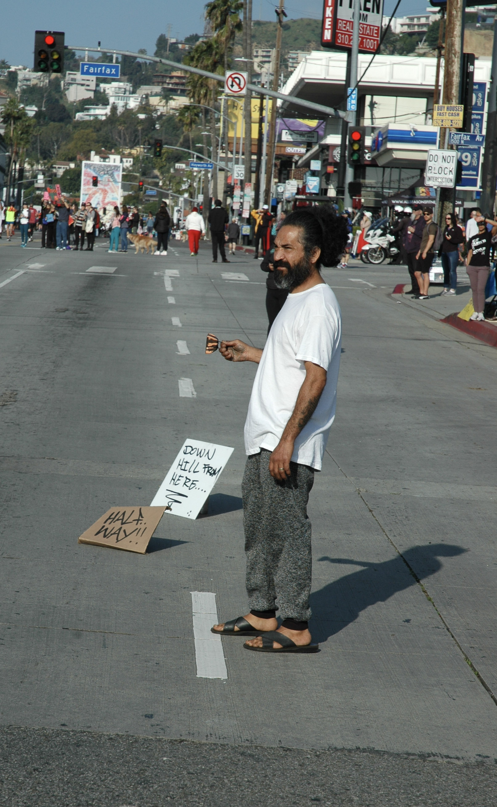 """A Los Angeles Marathon spectator marks the """"Half Way!!"""" point in the race, as he watches the marathon go by.  The half-way point of the race, mile 13, was located at the intersection of Sunset Boulevard and Fairfax Avenue in Los Angeles, California on March 24, 2019.  (Dakota Castets-Didier/The Corsair)"""