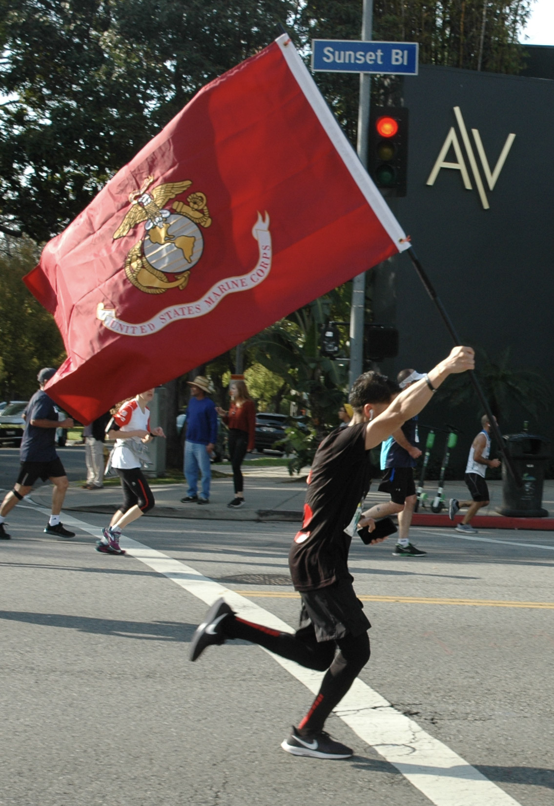 A runner participating in the Los Angeles Marathon waves a United States Marine Corps. flag as he approaches the half-way point of the race in Los Angeles, California, on March 24, 2019.  (Dakota Castets-Didier/The Corsair)