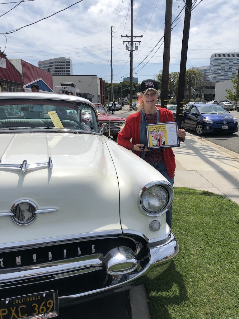 """Linda Dannels stands next to her 1955 Oldsmobile Holiday 88 at the All Women's Car Show and Vintage Fashion Exchange on Saturday, March 23, 2019, located at the Automobile Driving Museum in El Segundo, Calif. Dannels, who has attended the event for six years, proudly holds up her """"Top 12 Most Impressive Cars"""" award. (Mila Greenberg/The Corsair)"""