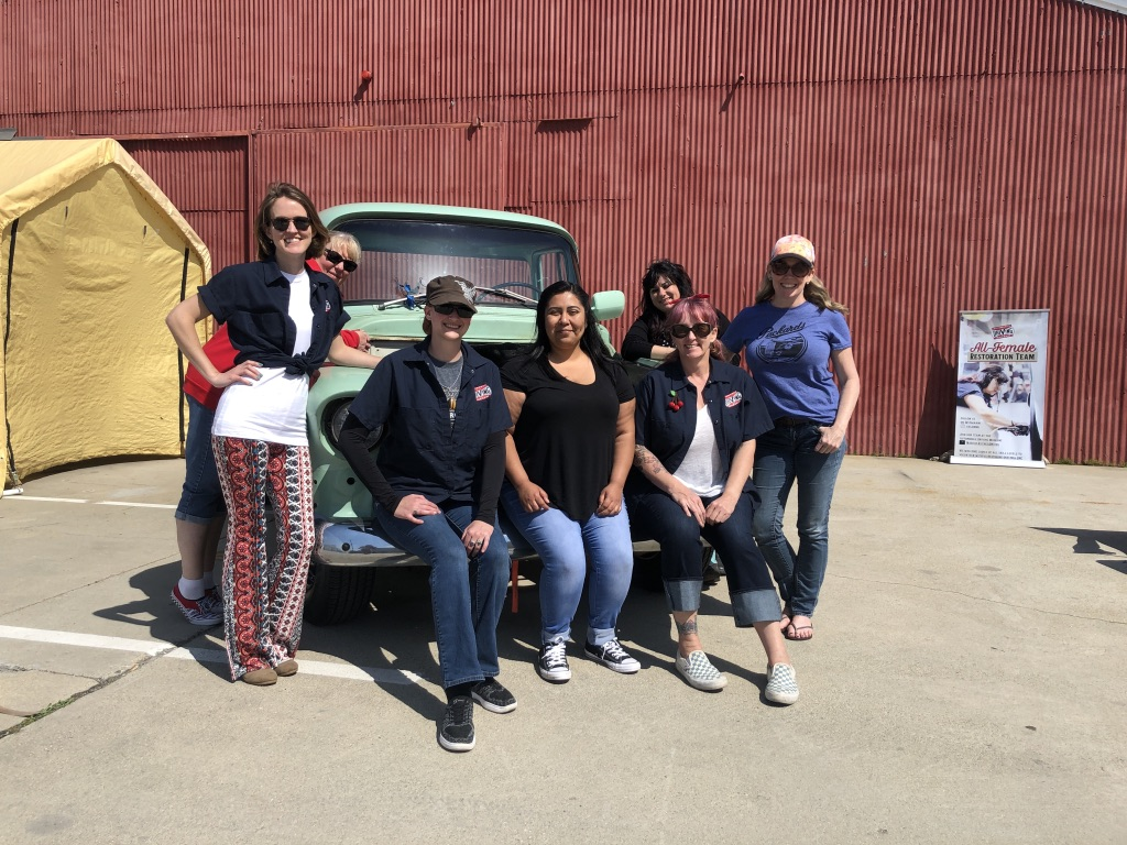 """Seven core members of the all-female restoration team surrounding their project: a 1955 GMC mint green pickup truck they named """"Jimmi."""" The team showed off their work on the truck so far at the All Women's Car Show and Vintage Fashion Exchange on Saturday, March 23 on the lot of the Automobile Driving Museum in El Segundo, CA. (Milla Greenberg/The Corsair)"""