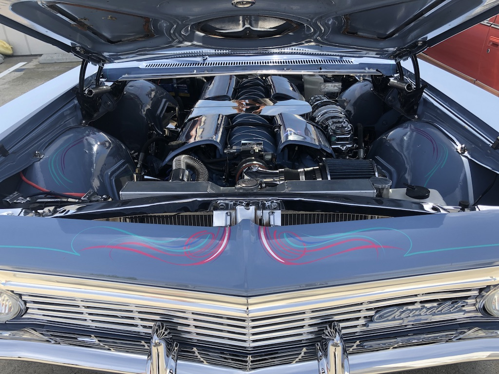 Woman shows off her 1966 Chevrolet engine in the lot of the Automobile Driving Museum on Saturday, March 23 in El Segundo, CA at the All Women's Car Show and Vintage Fashion Exchange. ( Milla Greenberg/TheCorsair)