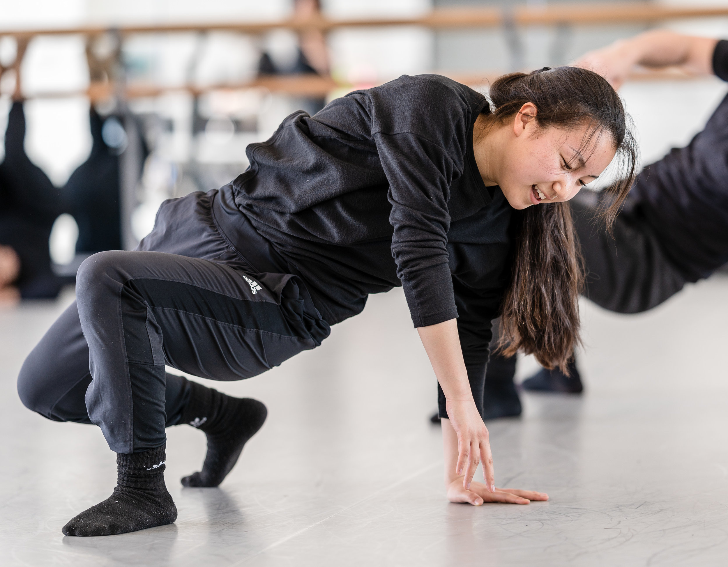 SMC student choreographer Aya Nakaguchi demonstrates a movement for the dancers in her not-yet-titled Synapse Dance Theater piece in the Core Performance Center (CPC) on Tuesday, March 12, 2019. Nakaguchi's choreographic concept started with a strict grid structure that allowed dancers to move across the stage, or upstage and downstage, but not on   diagonals or arcs. Nakaguchi said that as her rehearsals have progressed, the grid remains, but it has softened. Synapse Dance Theater will be presented on Friday and Saturday, May 24 and 25, on the SMC Broad Stage at the Performing Arts Complex (PAC) (Glenn Zucman/The Corsair)